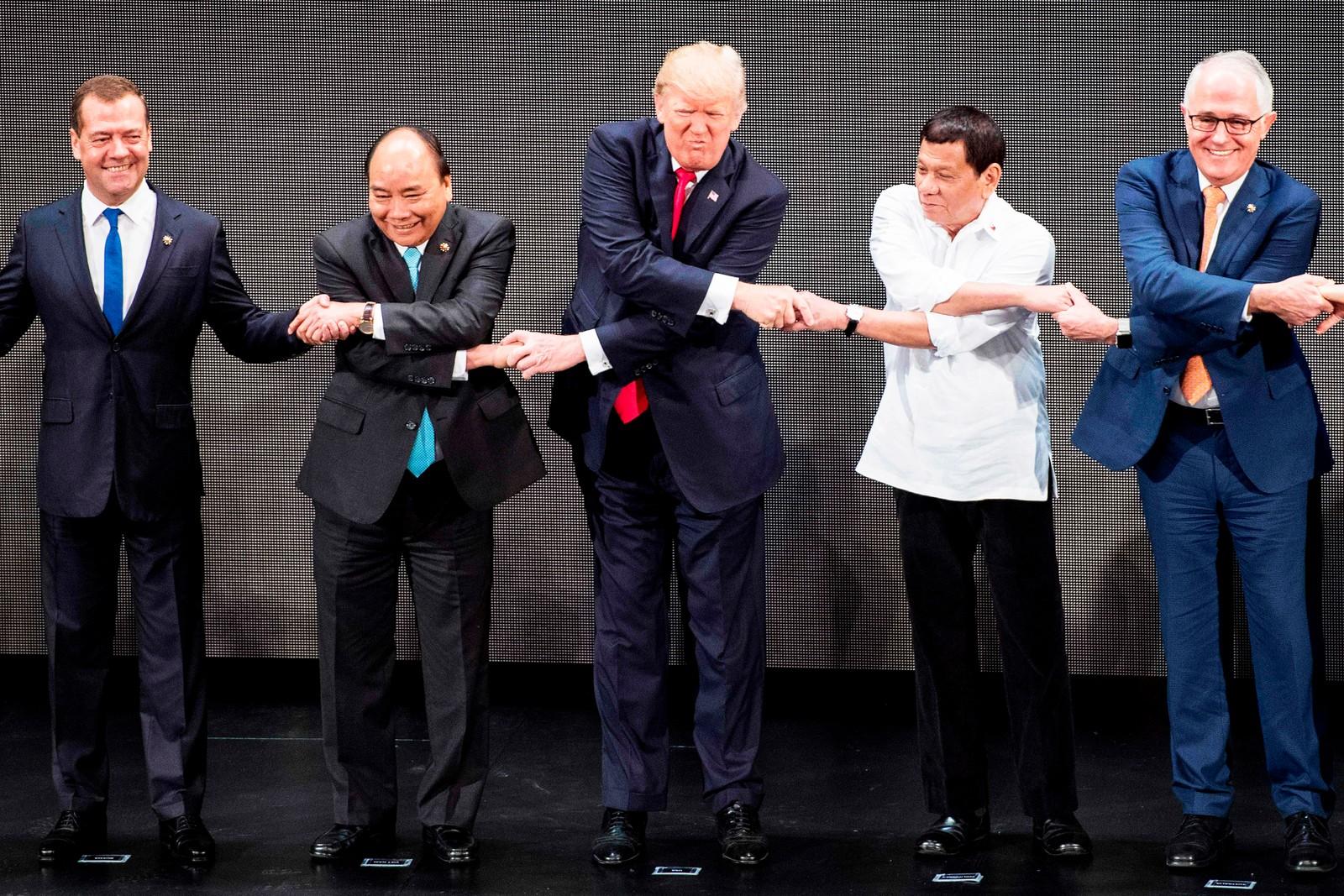 Også Russlands statsminister Dmitrij Medvedev (t.v.) lot være å ta «tversoverhåndtrykket» da han l fotografert sammen med Vietnams statsminister Nguyen Xuan Phuc (nummer to fra venstre), president Donald Trump (i midten) og Filippinenes president Rodrigo Duterte (nummer to fra høyre) Australias statsminister Malcolm Turnbull (til høyre) under toppmøtet i Manila.