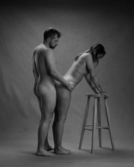 En naken mann med skjegg står på gulvet med armen rundt hoftene på en naken dame med tatoveringer og mørkt hår som lener hendene på en høy trekrakk med fire ben