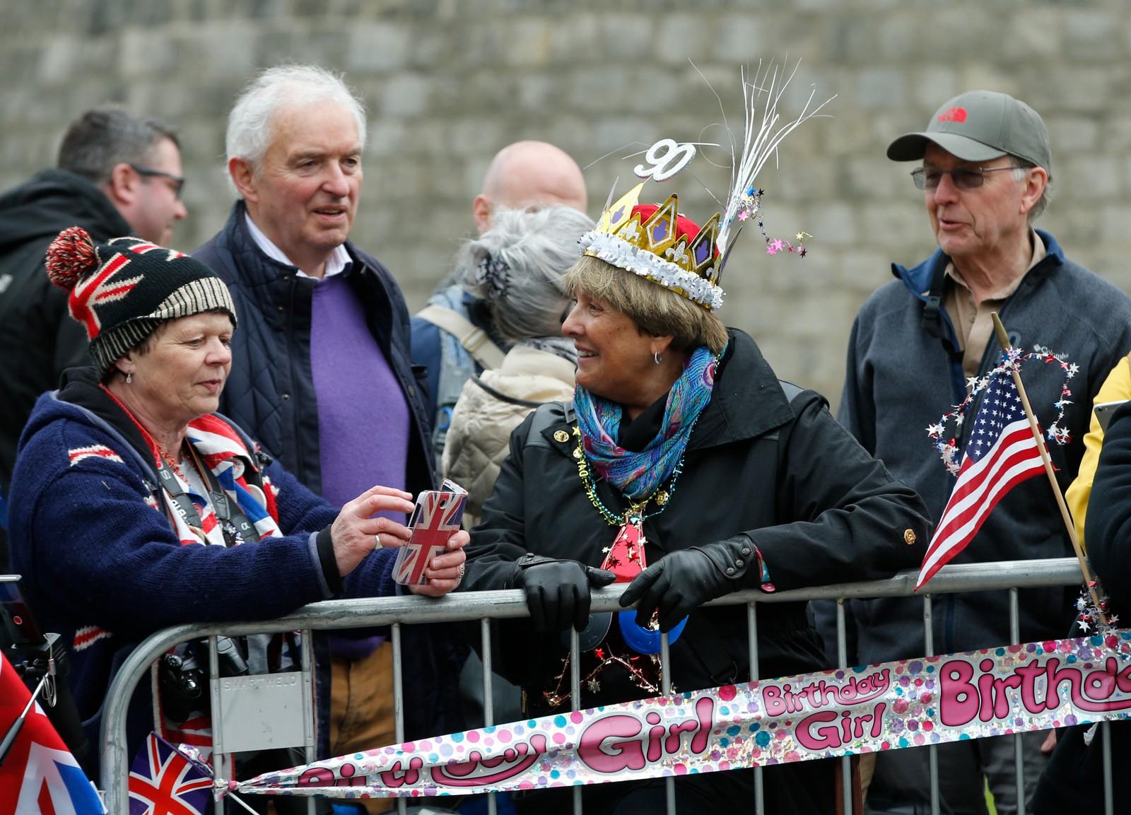 Kongelige fans står klar med plakater, flagg og ballonger i Windsor mens de venter på at dronningen skal vise seg.