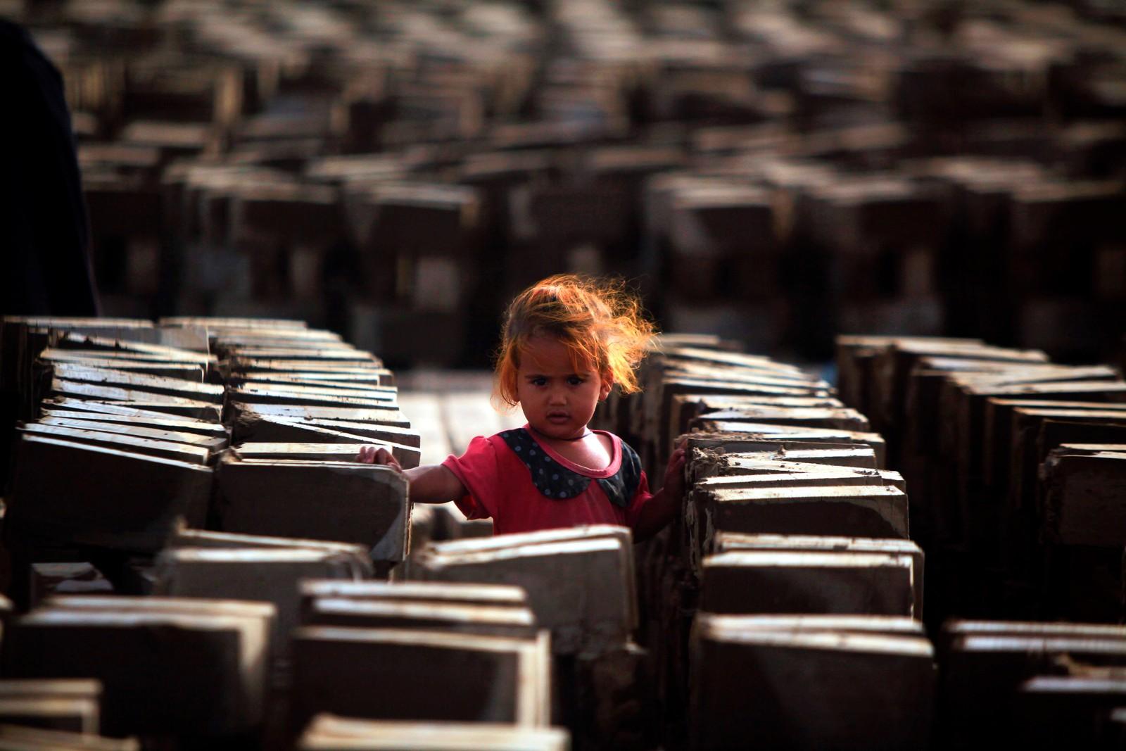 En jente står blant en mengde mursteiner ved en fabrikk i Najaf i Irak.