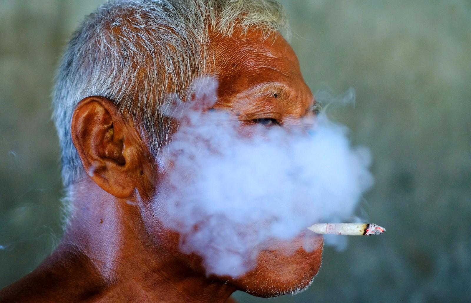 """""""Det finnes tre ting som ikke kan skjules: kjærlighet, røyk og en mann som rir på kamel."""" En arbeider tar seg en ordentlig røykepause på en fabrikk i Surakarta i Indonesia den 11. august."""