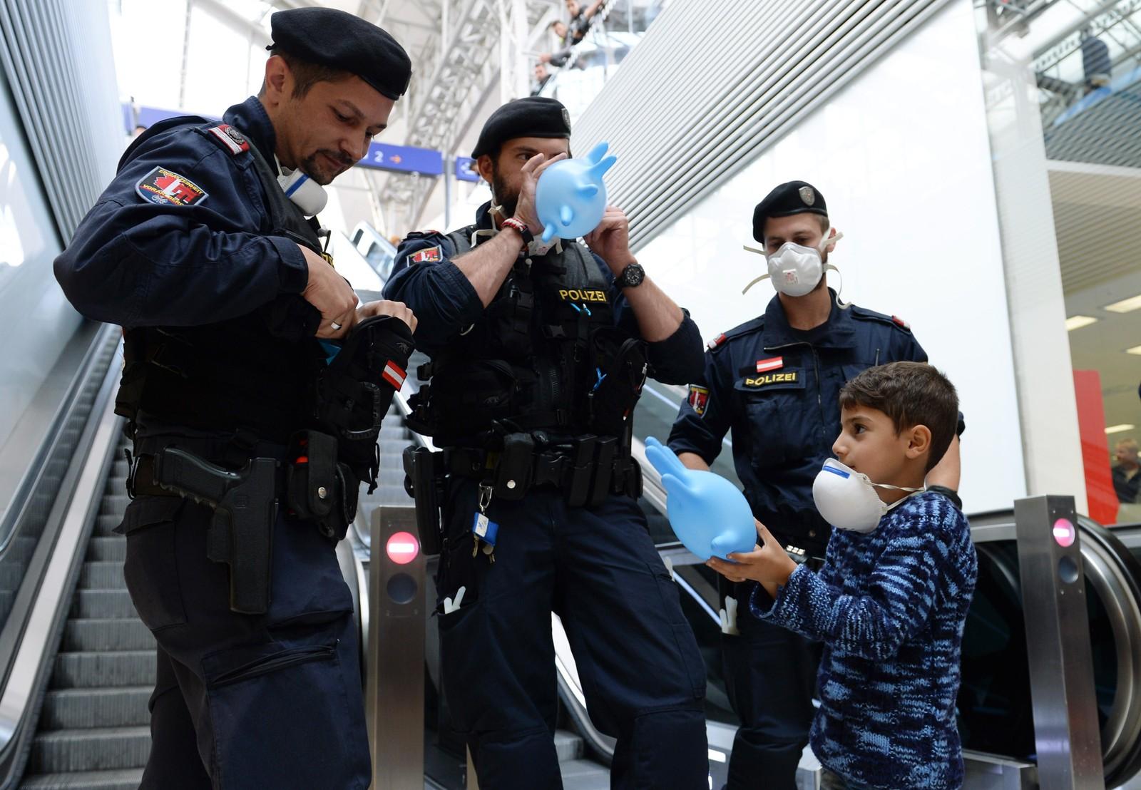 Østerrisk politi blåser opp hansker til ballonger for å underholde en flyktninggutt inne på togstasjonen i Salzburg. Titusenvis av syriske flyktninger har ankommet Østerrike og Ungarn de siste ukene.