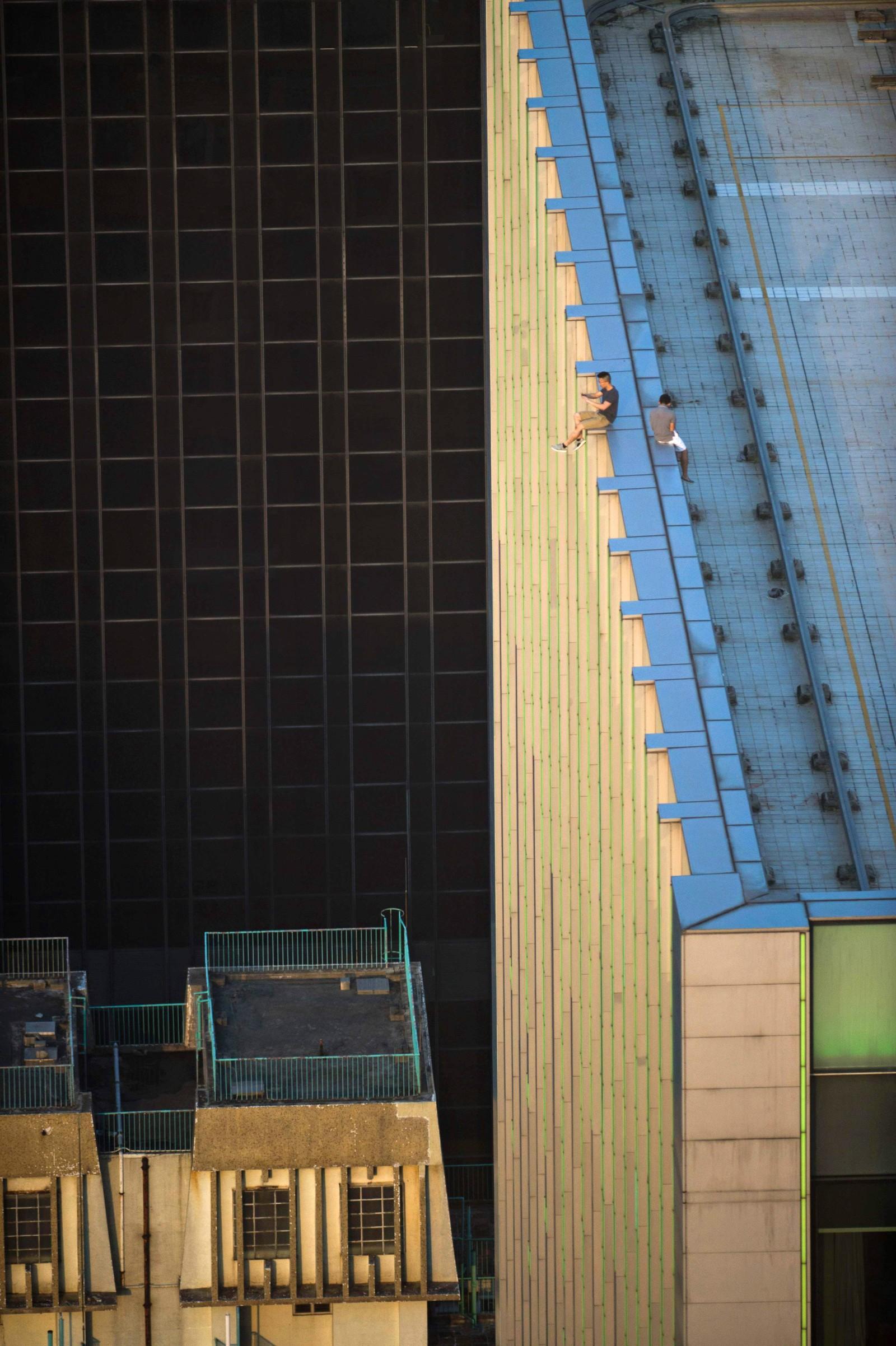 """Disse mennene driver med noe som blir kalt """"rooftopping"""". Det innebærer å komme seg opp på taket på de høyeste skyskraperne og ta spektakulære bilder av utsikten. Dette bildet er fra Hong Kong den 23. august"""