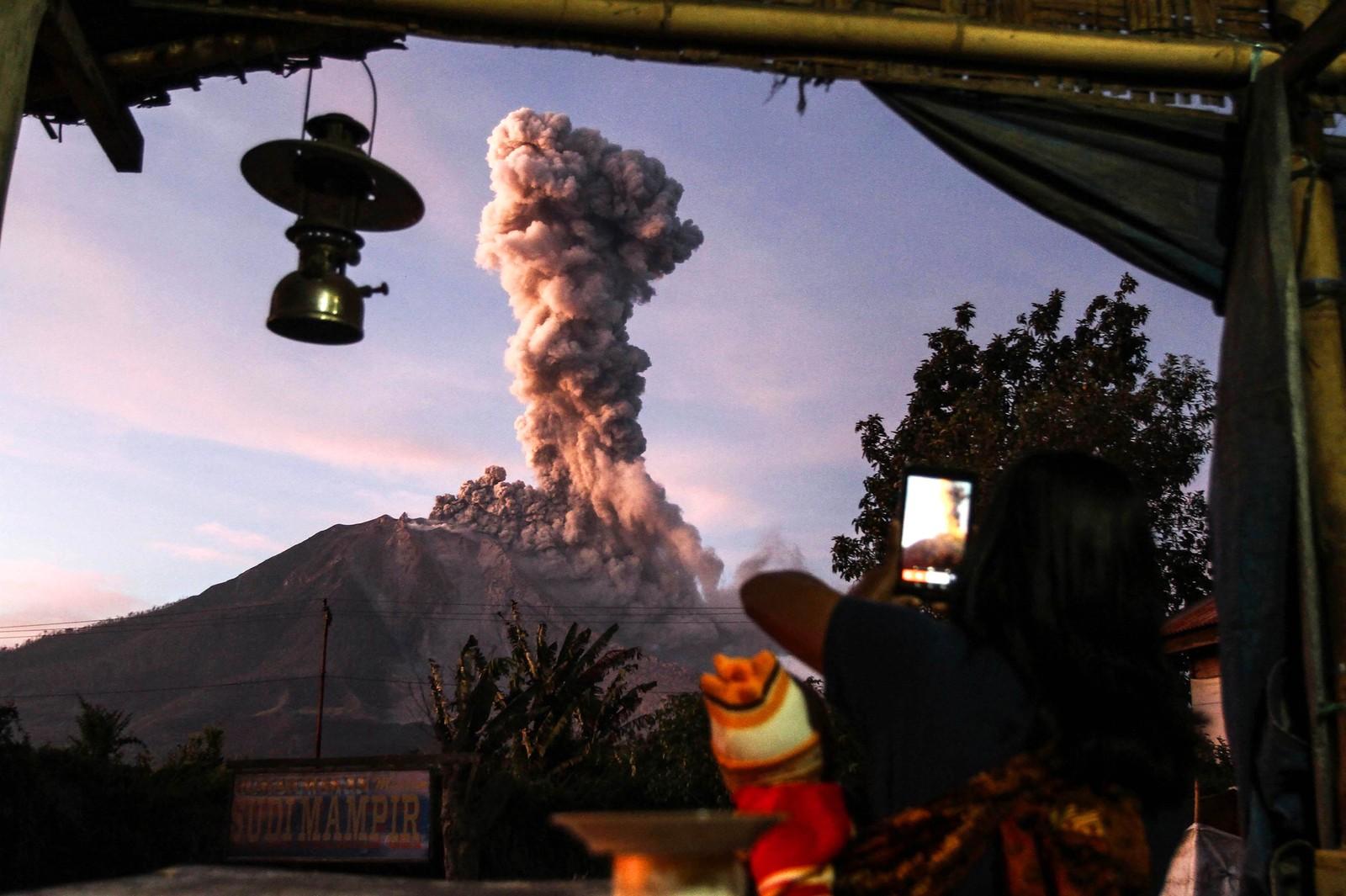 Vulkanen Sinabung i Indonesia er svært aktiv. En landsbyboer fra Tiga Pancur sikrer seg et bilde.