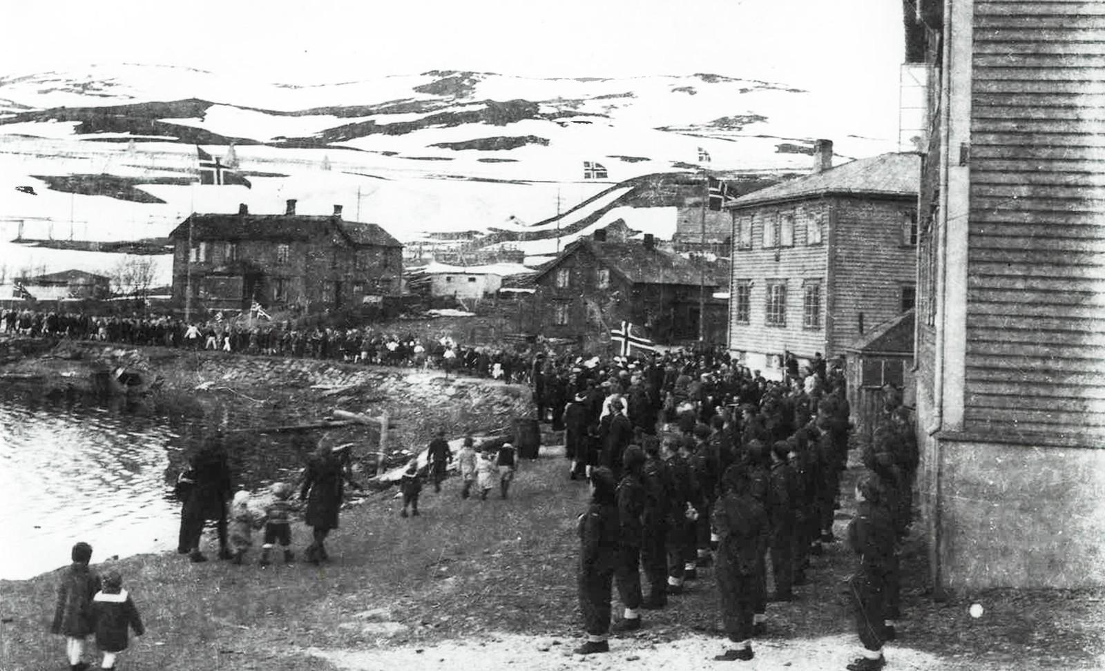 17. mai 1945: Togavgang fra Fiskarheimen. Norske soldater og lotter i forgrunnen. I bakgrunnen ser vi huset til Fritjof og Anna. Fritjof ble satt i varetekt på Fiskarheimen.