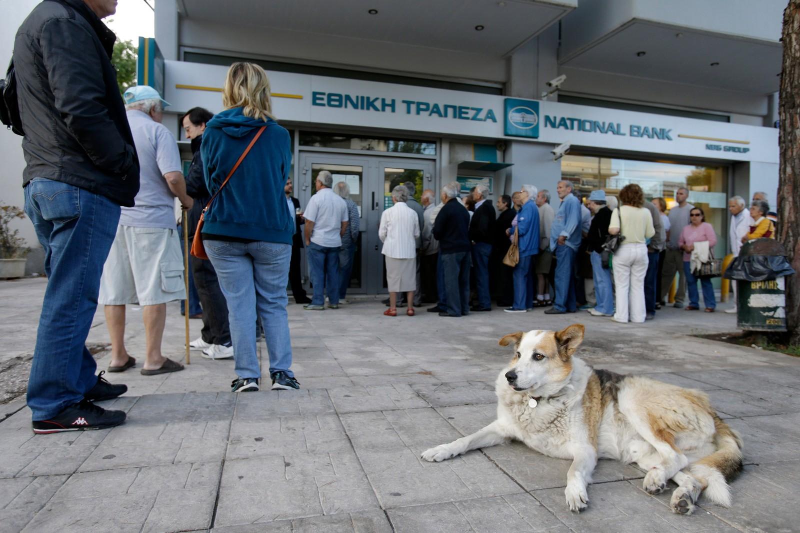 Pensjonister venter i kø utenfor en bank i Aten for å få ta ut penger, mens andre benytter minibanken på utsiden.