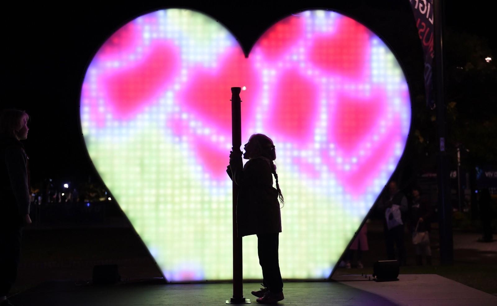 """Et barn roper """"I love you"""" mens et kjærlighets-barometer lyser opp i bakgrunnen. Vivid Sydney er en kulturfestival som arrangeres årlig i, nettopp, Sydney, Australia."""