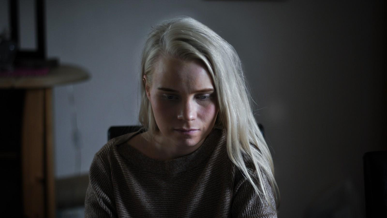 Nærbilde av Sara. Lyset faller inn fra høyre og lyser opp håret og ansiktet på høyre side. Blikket er vendt ned. Uskarp og litt mørk bakgrunn.