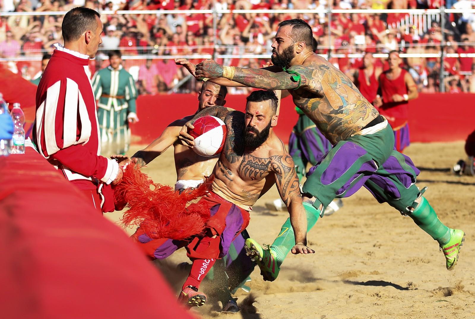 Det kalles Calcio Fiorentino, og arrangeres én gang i året i Firenze. Sporten stammer fra 1600-tallet. Fire klubber kjemper om å vinne de rugby-lignende kampene, der det meste er tillatt så lenge ikke flere angriper samme mann. Kampene spilles på sandbaner og varer i 50 minutter. Den som har fått ballen flest ganger i mål vinner. Her ser vi lagene Santa Maria Novella og San Giovanni barke sammen.