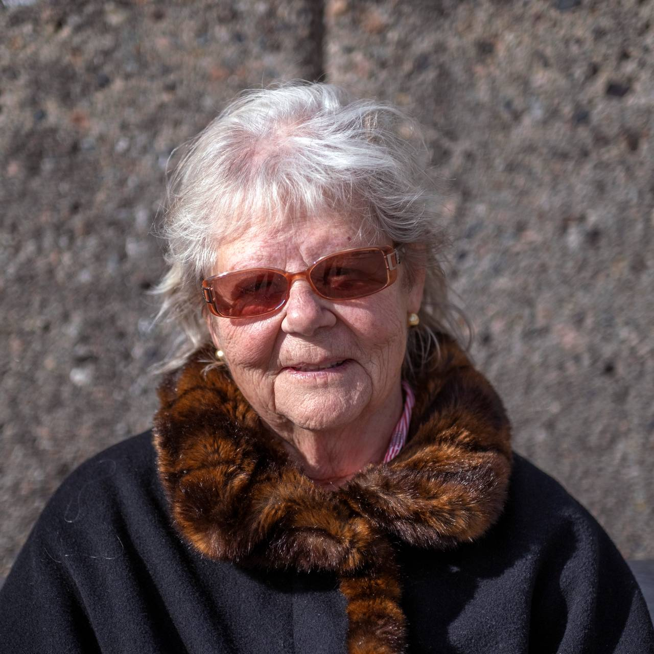 Greta Arnhol sit på ein benk på Aker brygge i Oslo