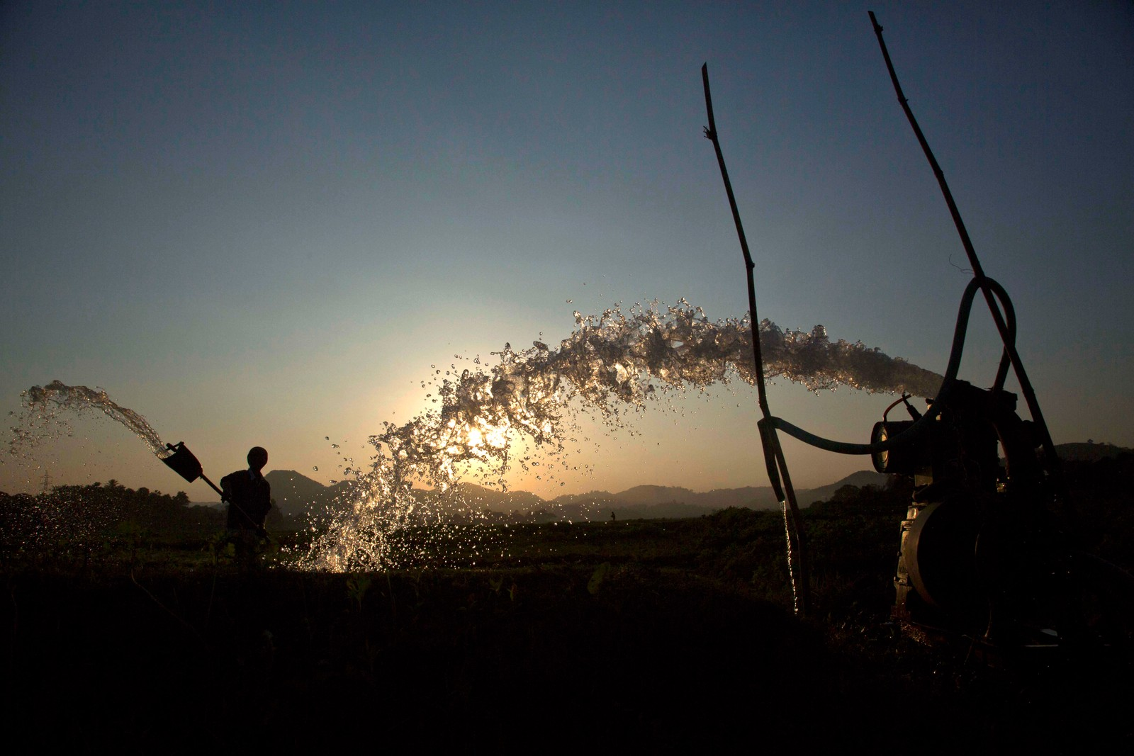 En indisk bonde vanner risåkeren sin utenfor Gauhati i India. Mer enn 70 prosent av Indias 1,25 milliarder mennesker lever av jordbruk.