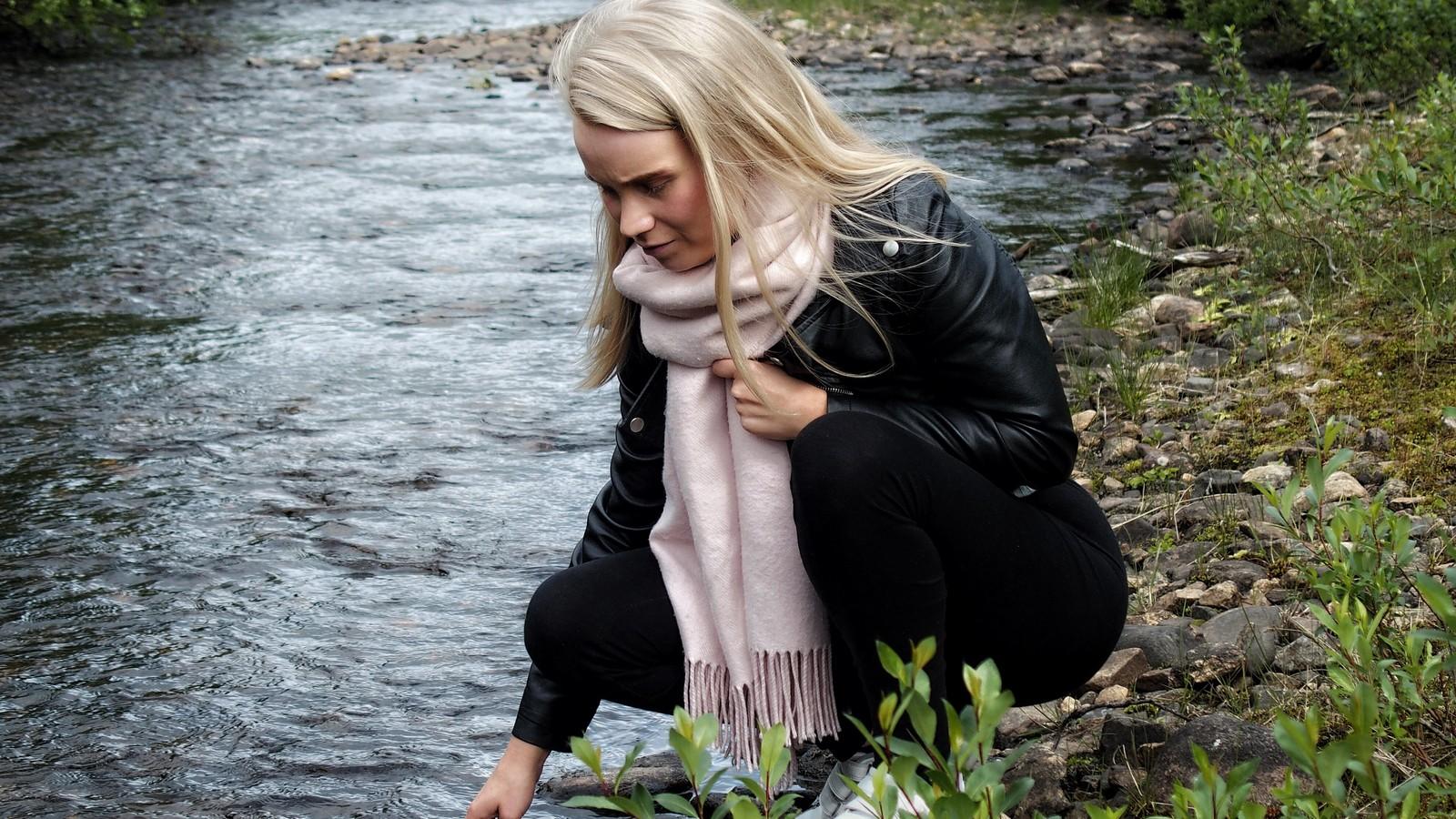 Sara sitter på huk ved elvebredden og kjenner på vannet med høyre hånd. Med venstre hånd stryker hun bort sitt lange lyse hår fra ansiktet.