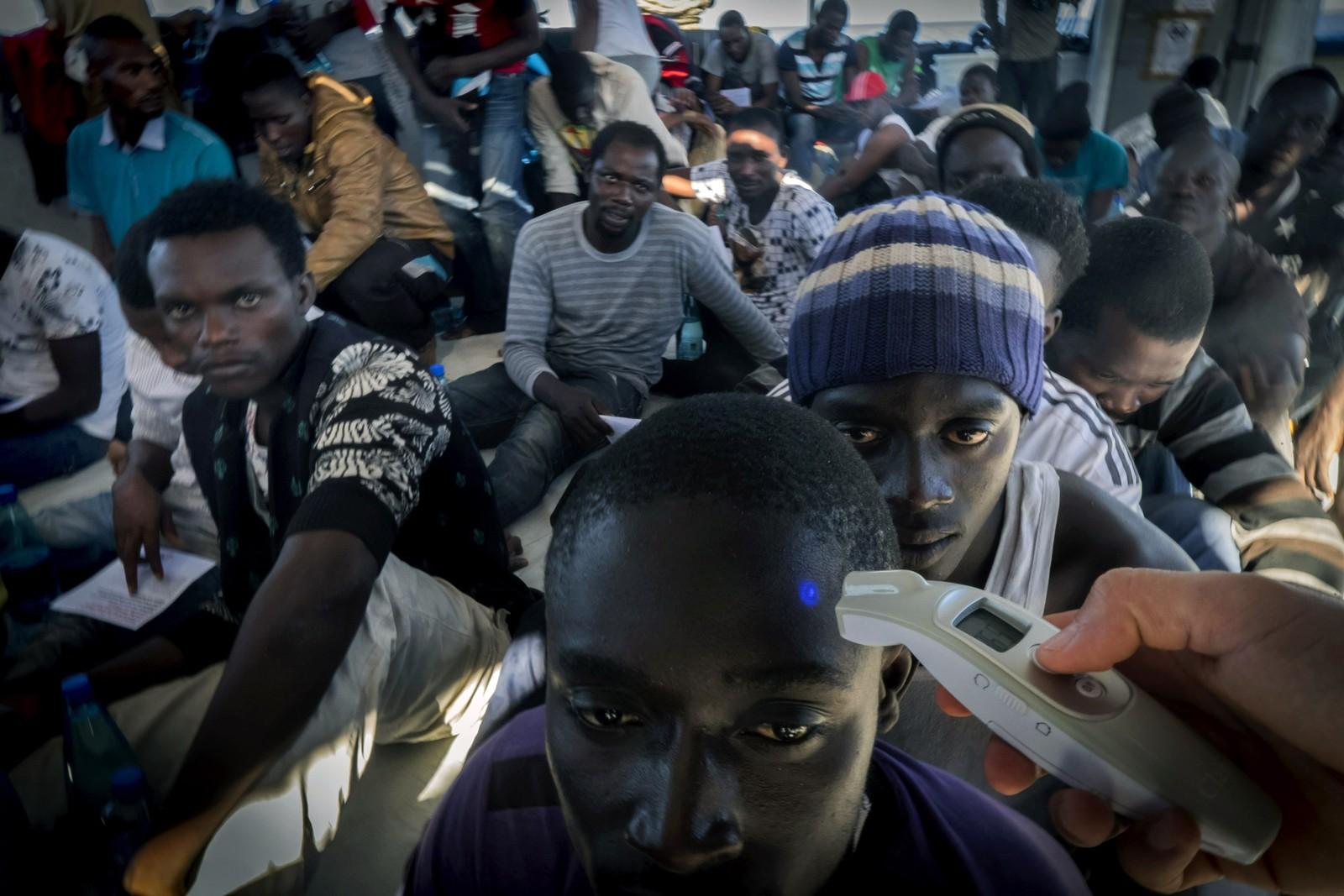 En representant for Leger uten grenser sjekker temperaturen på en av flyktningene ombord på båten Dignity 1 på vei fra Libya over Middelhavet.
