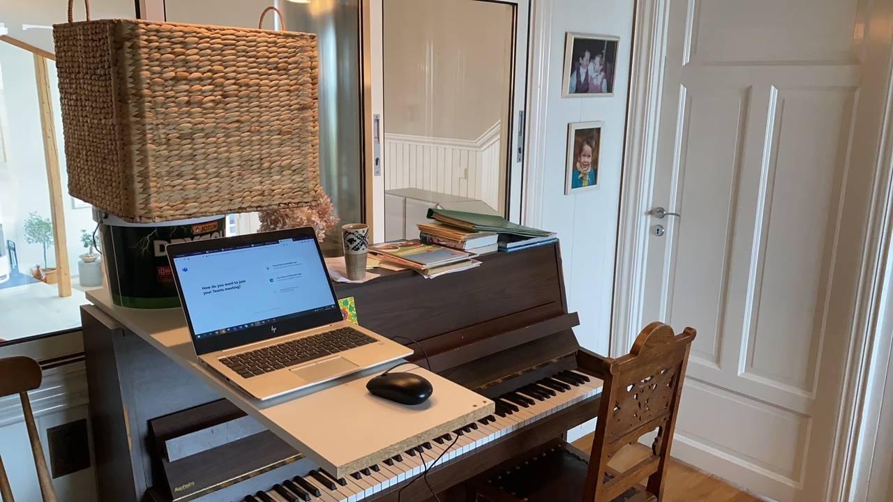 Hjemmekontor. For å få ståbord har han stablet en bordplate oppå et piano. Et malingsspann og en stor kurv er motvekt til PC og mus.