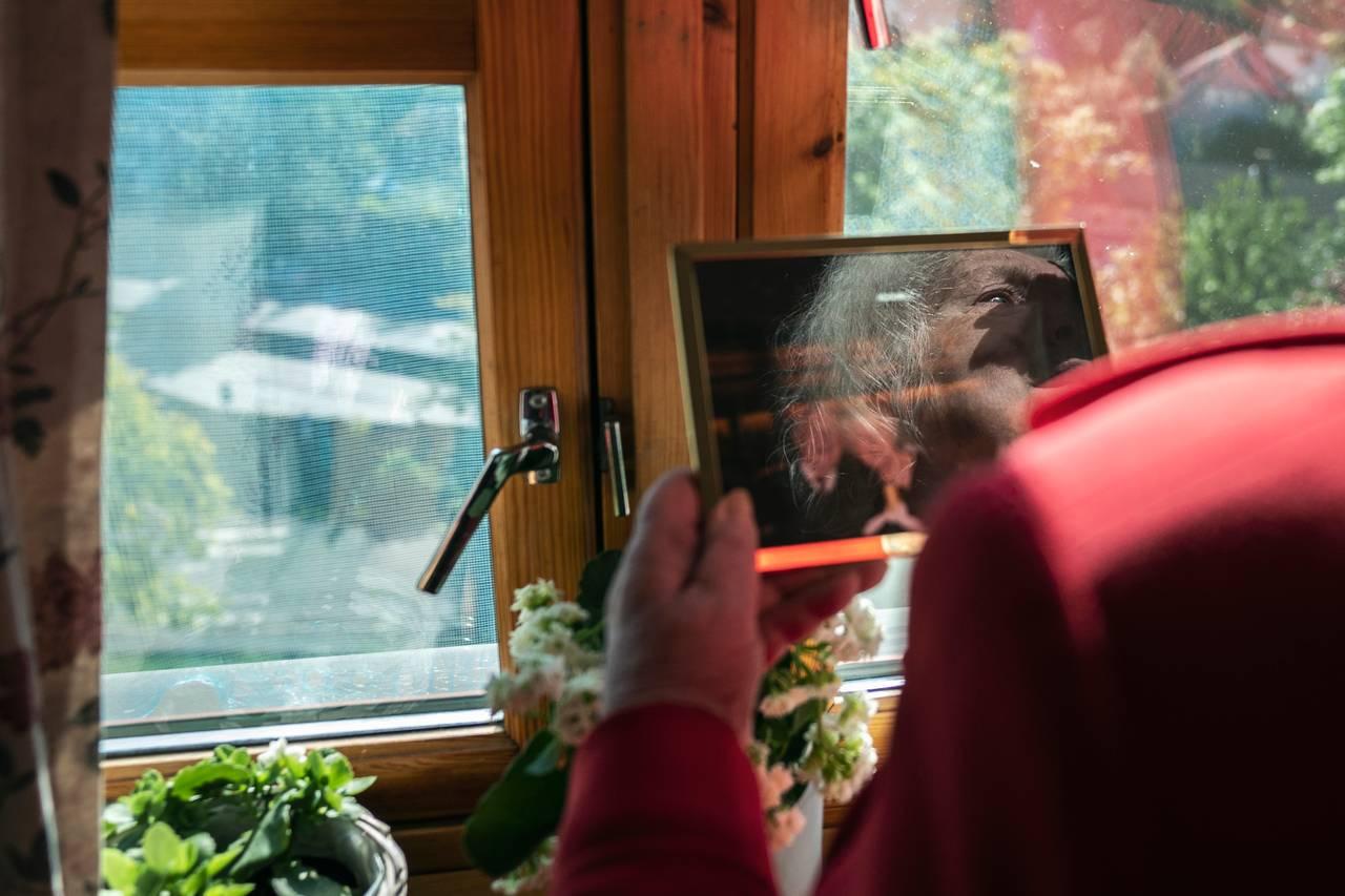 Kvinne i rød jakke ser på et innrammet bilde i vinduet. I refleksjonen på bildet ser man tårer i øynene hennes.