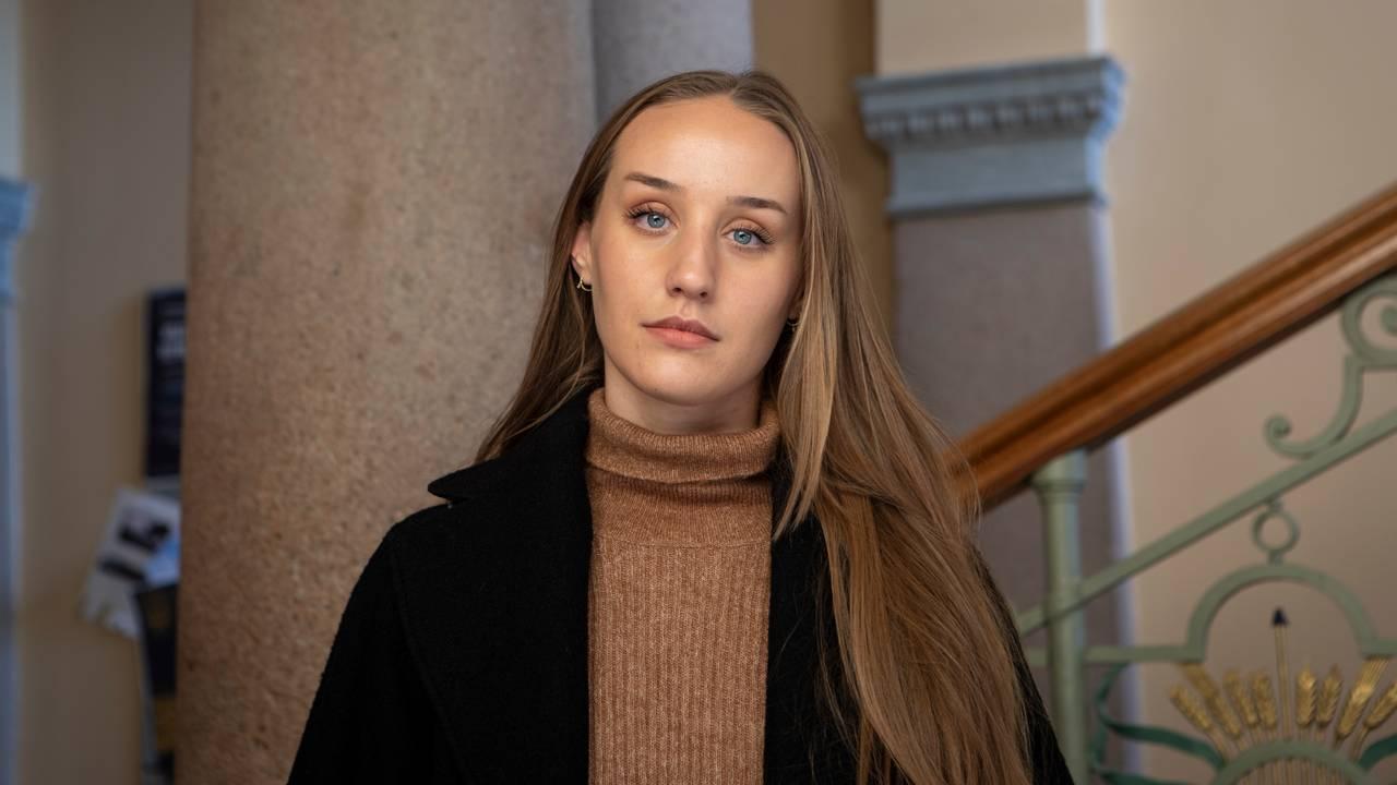Portrett av Ingvild Dagsland. Hun har på en brun genser og sort kåpe. I bakgrunnen ser man så vidt skolens inngangsparti, med store søyler og en gammel utsmykket trapp.