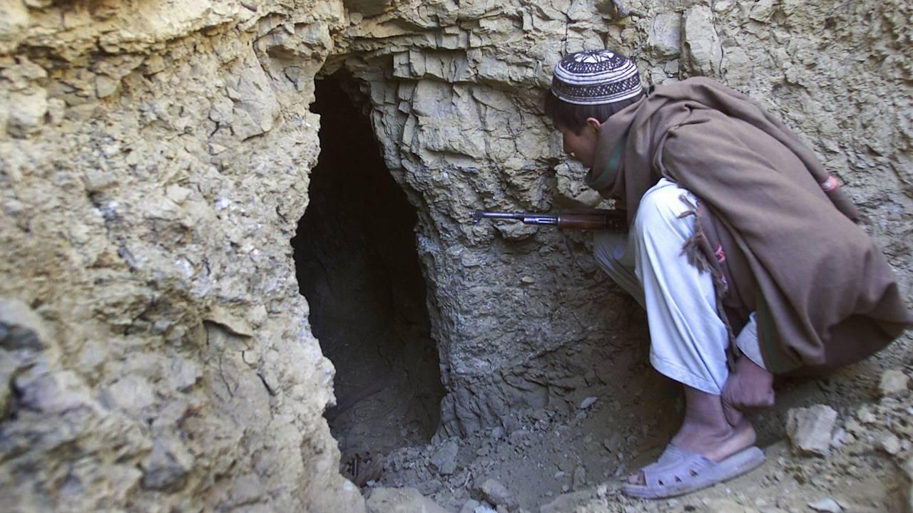 En afghansk mann som er mot Al Qaida titter i en hule i De hvite fjellene som terrorgruppen brukte til våpenlagring. En treningsleir lå like ved. Bildet er tatt 18. desember 2001.
