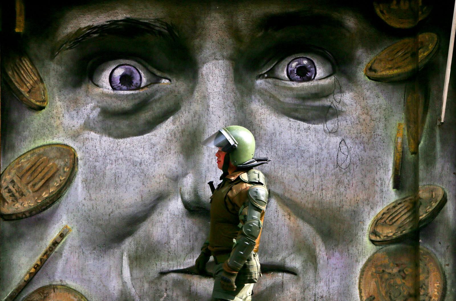 En politimann går forbi et veggmaleri under en demonstrasjon i Santiago i Chile. Mennesker var samlet for å demonstrere mot det de mener er dårlige pensjonsrettigheter.
