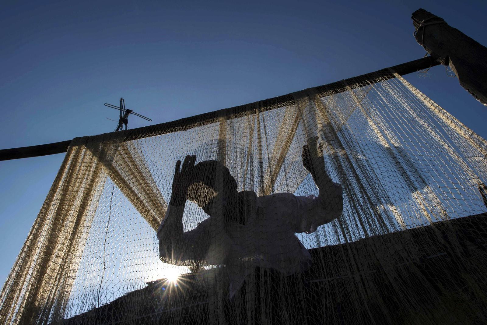 En fisker henger opp garn ved elven Irrawaddy i Myanmar.