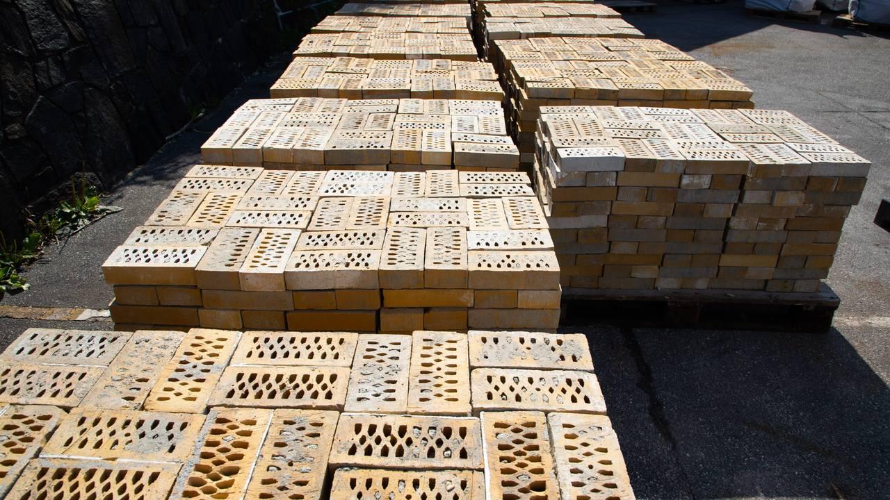 Et titalls europaller fullastet med murstein ligger på to rekker på anleggsplassen. Stablene er rundt 1 meter høye. Steinene er rene og ferdig pusset.