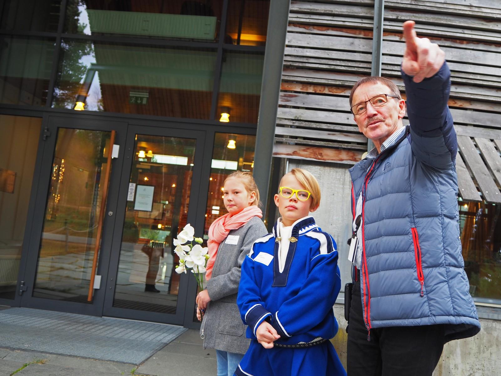 VISER: Sametingets Kåre Balto peker til der de kongelige ankommer med bilen sin.