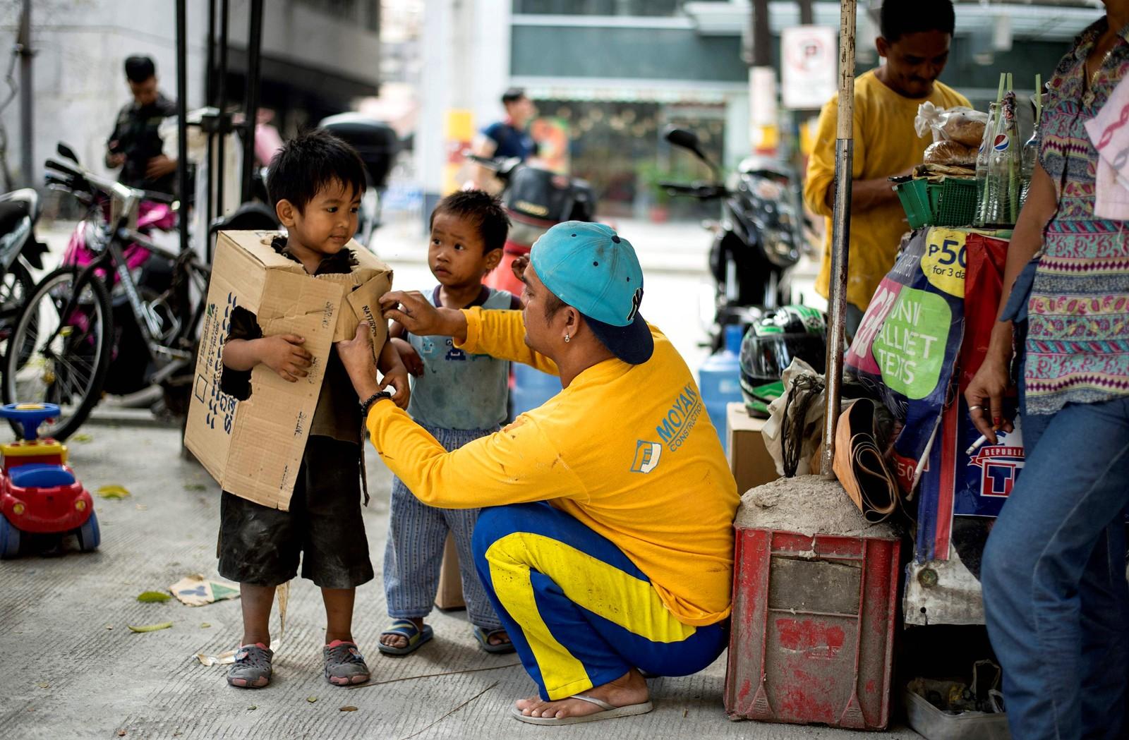 En liten gutt gir en bygningsarbeider et takknemlig blikk når han er i ferd med å få et robotkostyme på seg.