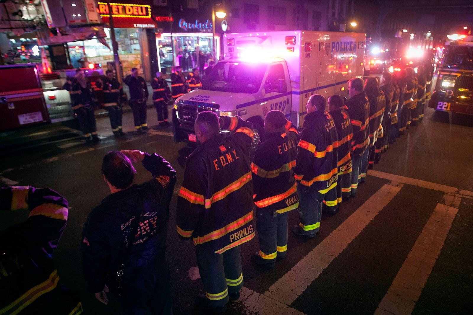 New Yorks brannmenn gjør honnør mens ambulansen med en av de drepte kjører forbi.