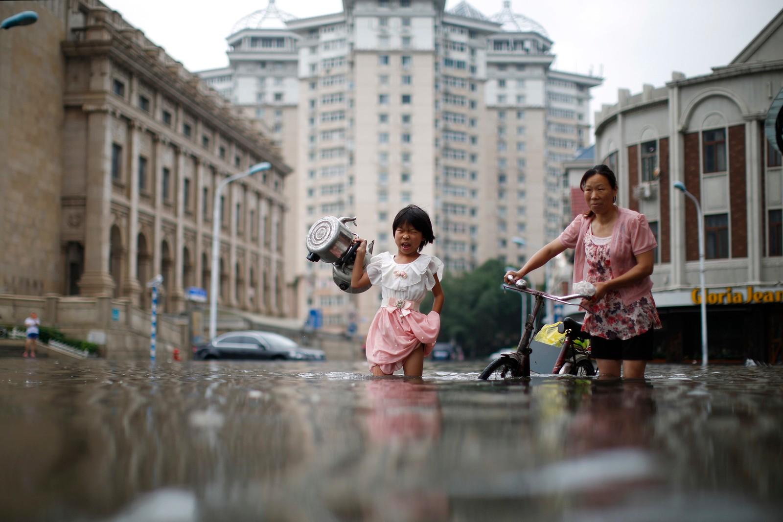 Et barn bærer en kjele gjennom det som til vanlig er en gate i Tianjin