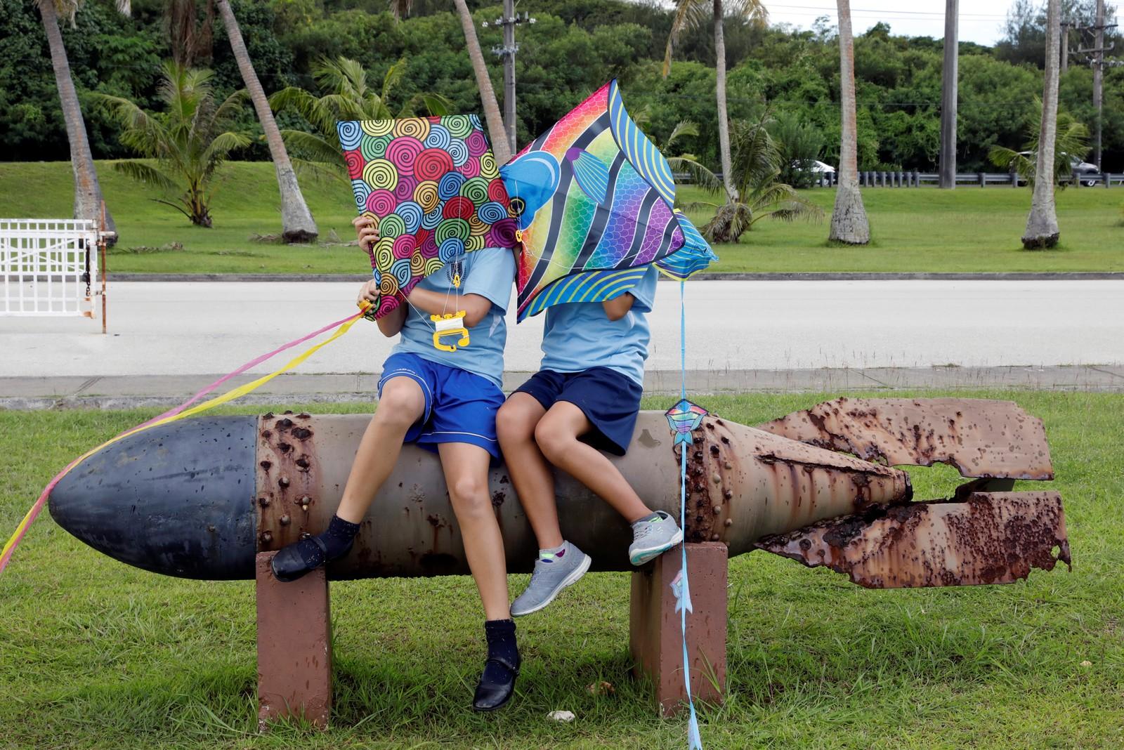 To skoleelever sitter med dragene sine på restene av en torpedo fra andre verdenskrig i Asan Memorial Park på stillehavsøya Guam, som er amerikansk territorium. Ordkrigen mellom USAs president Donald Trump og Nord-Koreas leder Kim Jong-un har eskalert de siste dagene og atomtrusselen har spisset seg til.