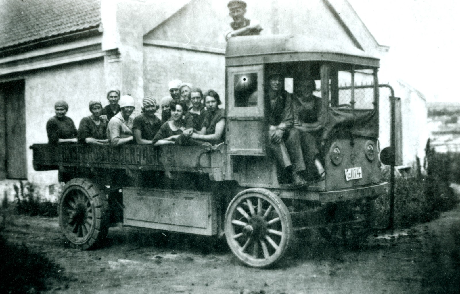 """Ansatte på lasteplan. Udatert. Bak på bildet står det El-bilen. Bilen ble kjøpt i 1924 – ble kalt """"Padda"""" og gikk på elektrisitet. Kjørte hampballer med den. Tidligere brukte man hest."""
