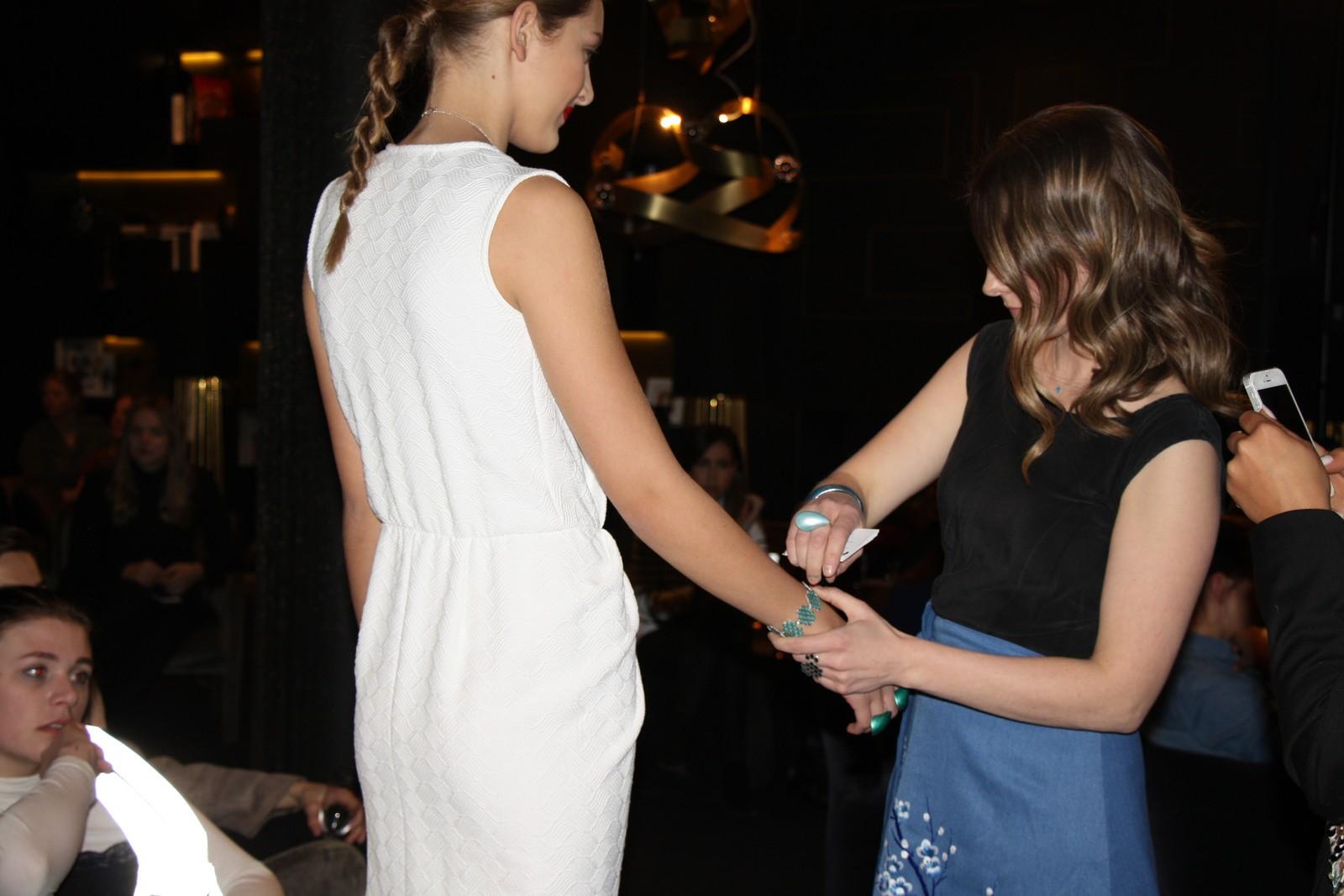 Linn Sigrid Bratland fester armbånd på en modell.