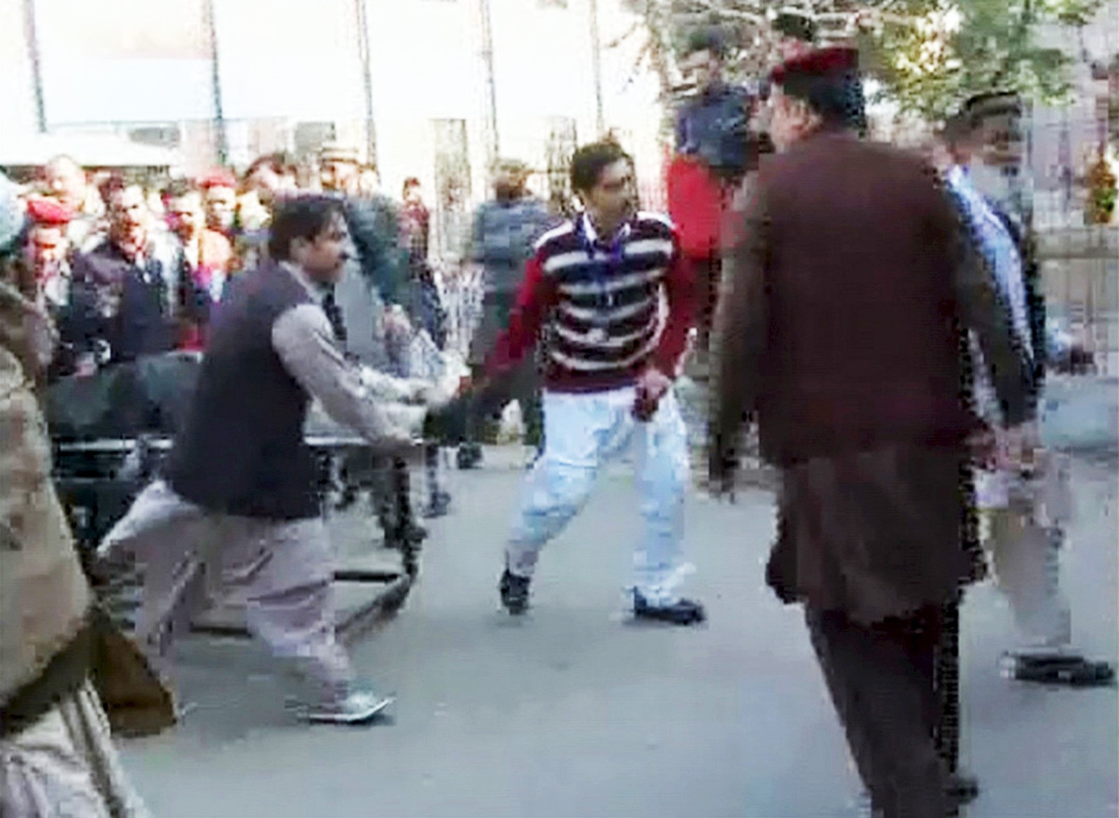 Folk bærer en såret person på båre på Bacha Khan-universitetet