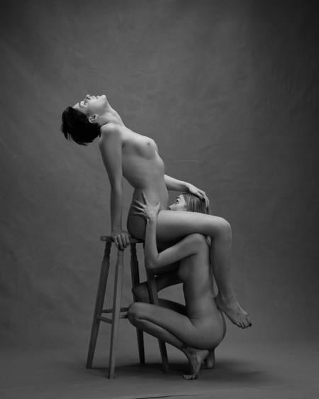 En kvinne med kort mørkt hår sitter på en krakk og løfter hodet bakover mens hun holder øynene lukket. Hun har løftet det ene beina over skulderen til en annen blond kvinne. Den andre kvinnen sitter med ansiktet mellom beina hennes og simulerer oralsex. Begge er nakne, men kjønnsorganene er ikke synlige.