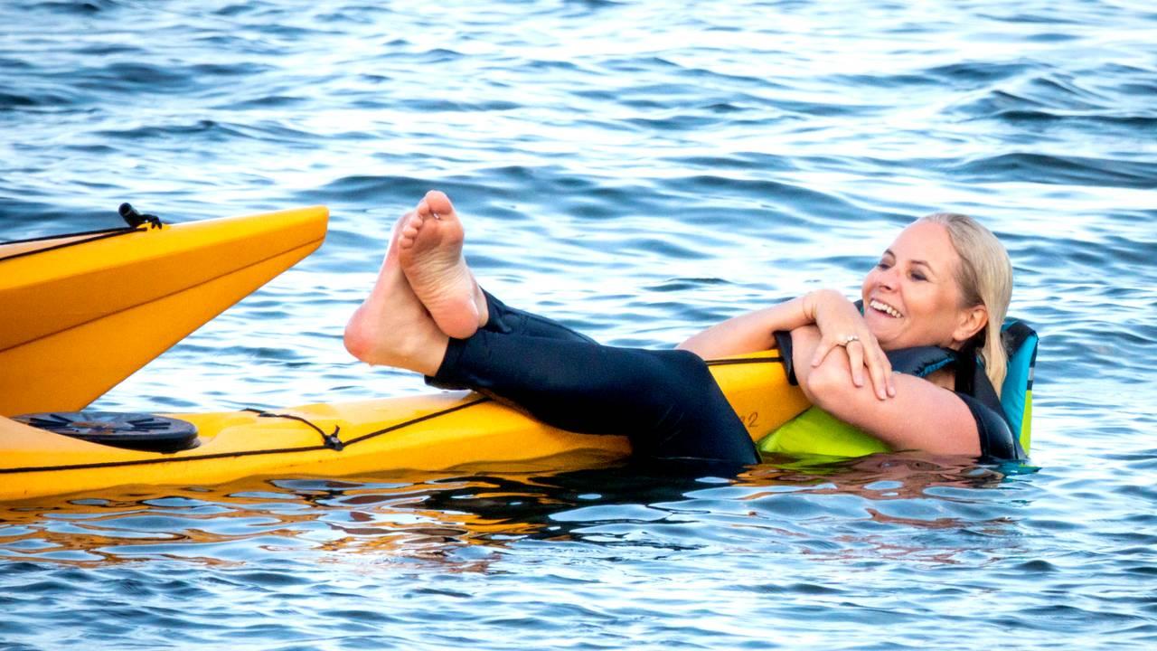 Kronprinsesse Mette-Marit ligger i vannet og holder seg fast i kajakken