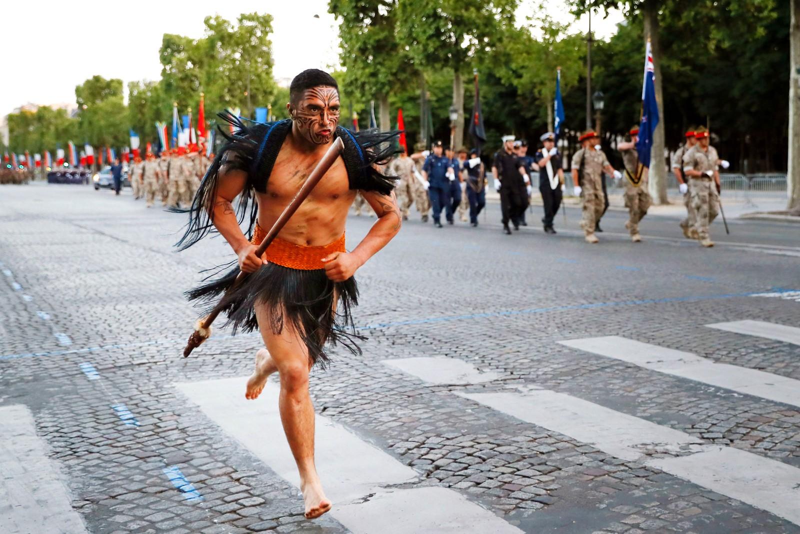 En Maori løper ned Champs Elysees i Paris under en øving til Bastille-dagen den 12 juli. Maoriene er et urfolk fra New Zealand. I bakgrunnen marsjerer soldater fra hjemlandet hans. Bastille-dagen er Frankrikes nasjonaldag, og feires den 14.juli.