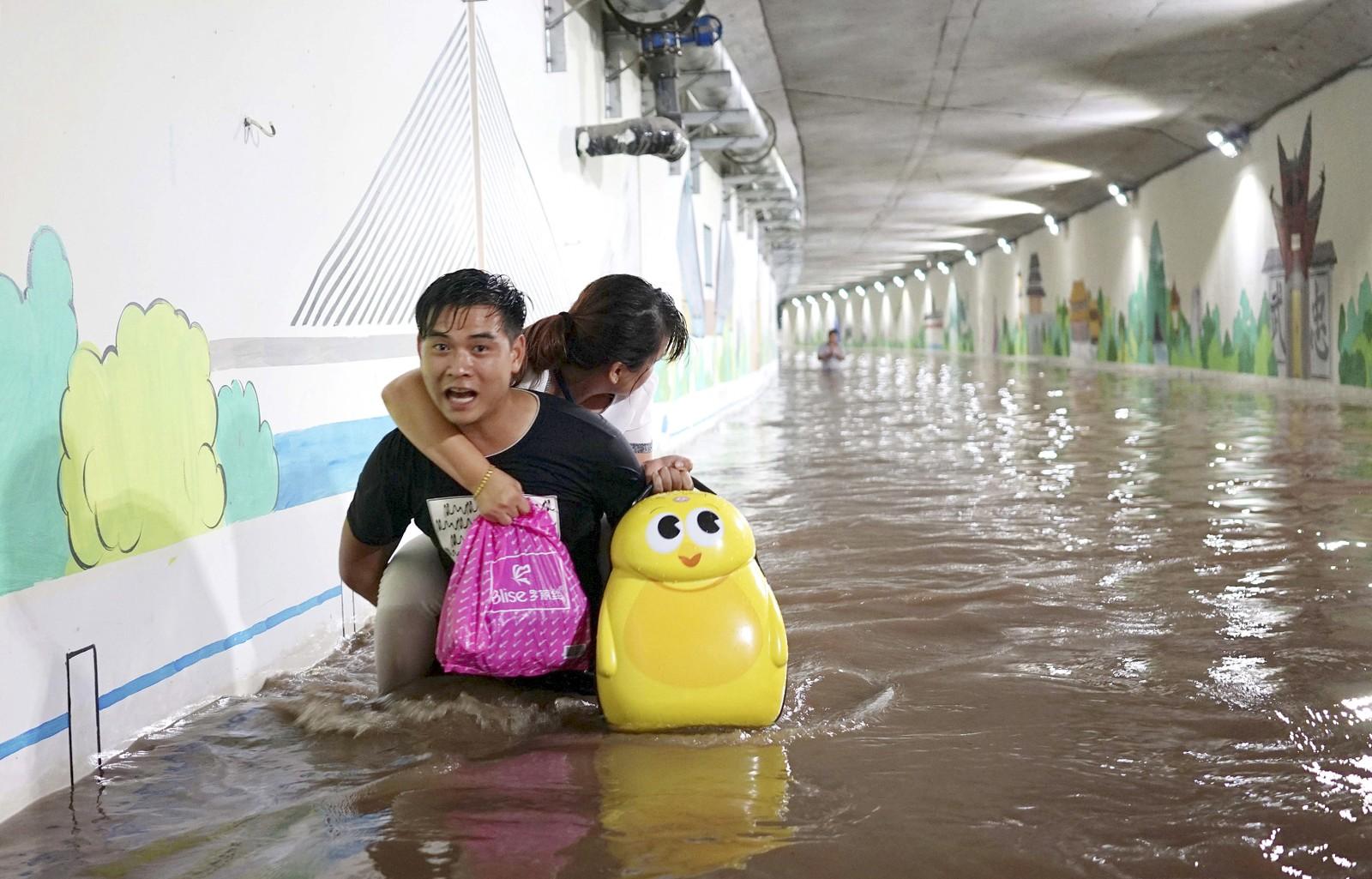 Dette paret er på vei til toget for å komme seg vekk fra det flomrammede Jinjua-distriktet i Kina.