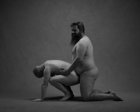 En naken mann sitter på huk på gulvet mens han ser ned i bakken og støtter seg på strake armer. En skjeggete naken mann står på kne bak rumpa hans og holder ham rundt magen