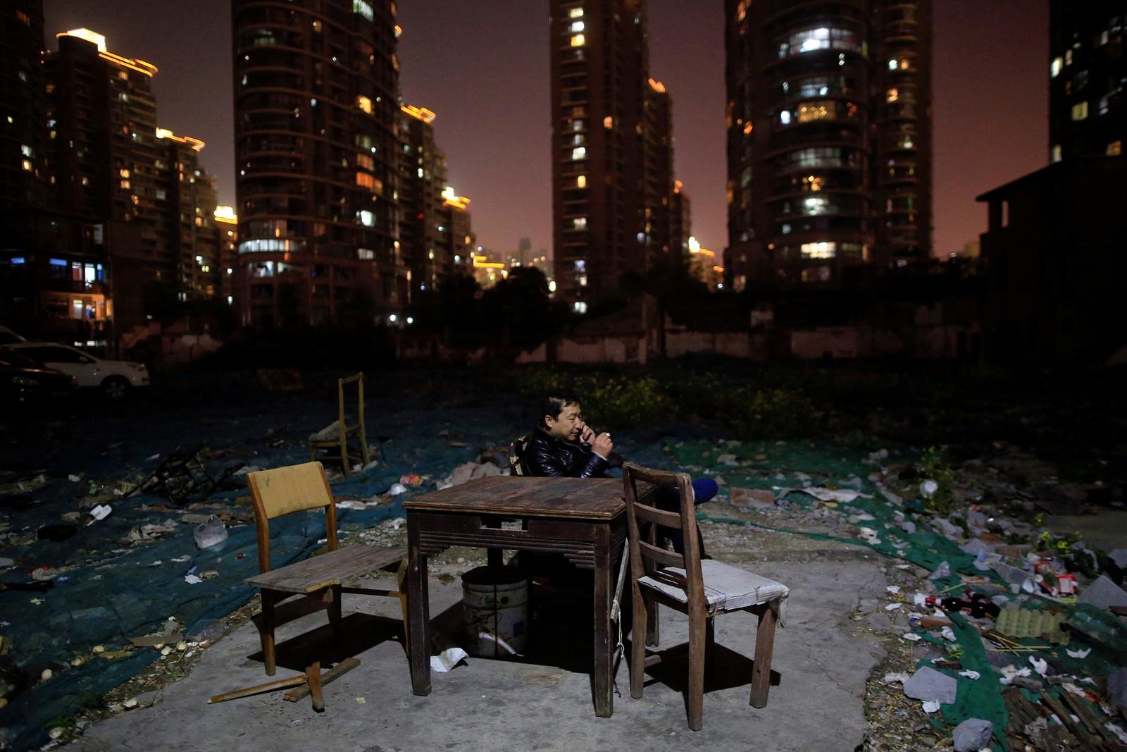Li Guoqiang snakker i telefonen i utenfor huset sitt i Guangfuli-nabolaget i Shanghai. Området er boligmegleres våte drøm, og skal være verdt enorme summer i et av verdens heteste boligmarked. Fastboende nekter imidlertid å flytte, melder nyhetsbvyrået Reuters.