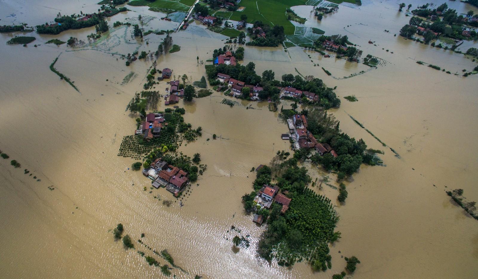 Hus og åkrer er delvis under vann i Gaoyang i Hubei-provinsen. Flere titalls er døde eller savnet siden flommen begynte mandag