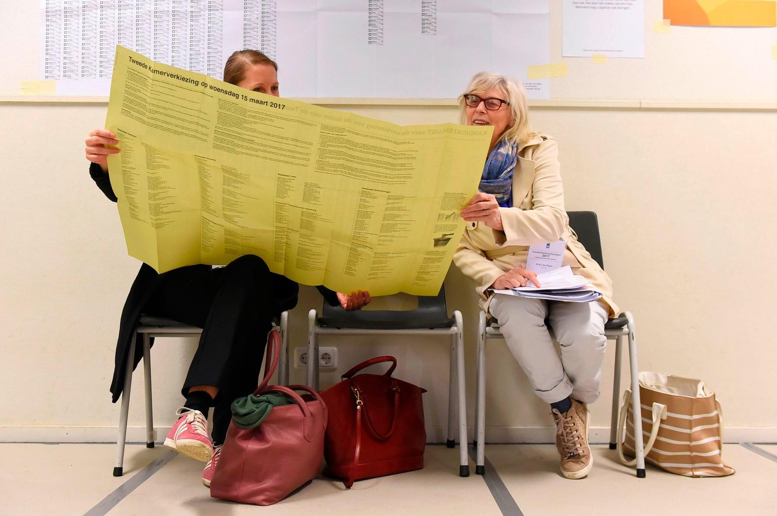 Her var det litt å sette seg inn i. To kvinner leser valginformasjon ved et stemmelokale i Haag i Nederland.