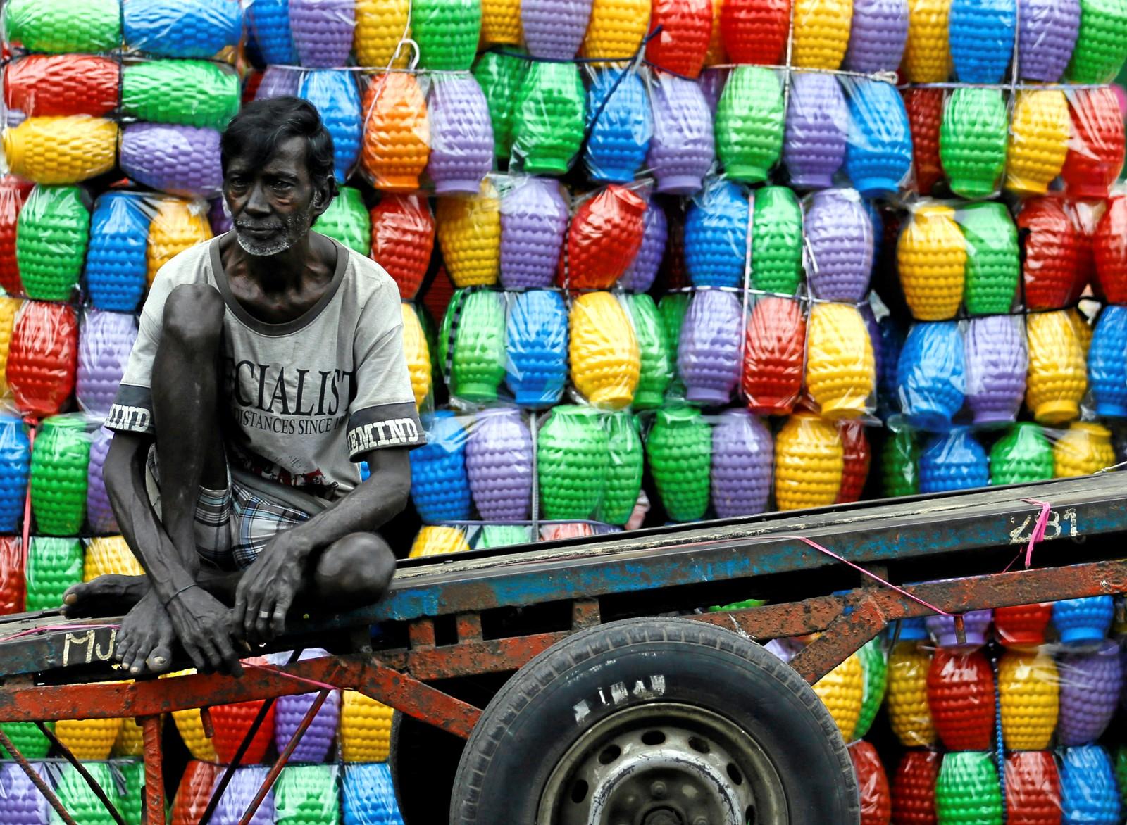 Han har nettopp lastet av alle plastikkmuggene fra vognen ved et marked i Colombo I Sri Lanka.