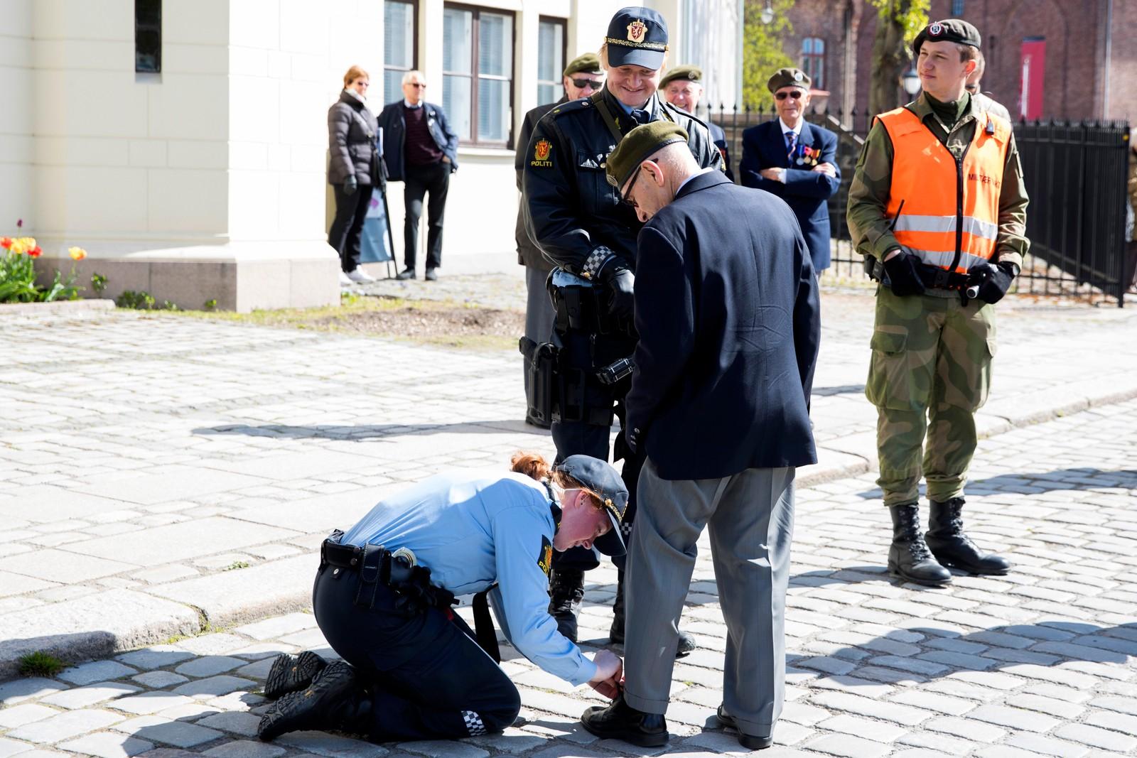 En militær-veteran får hjelp med skolissen under et arrangement i forbindelse med frigjørings- og veterandagen 8. mai.