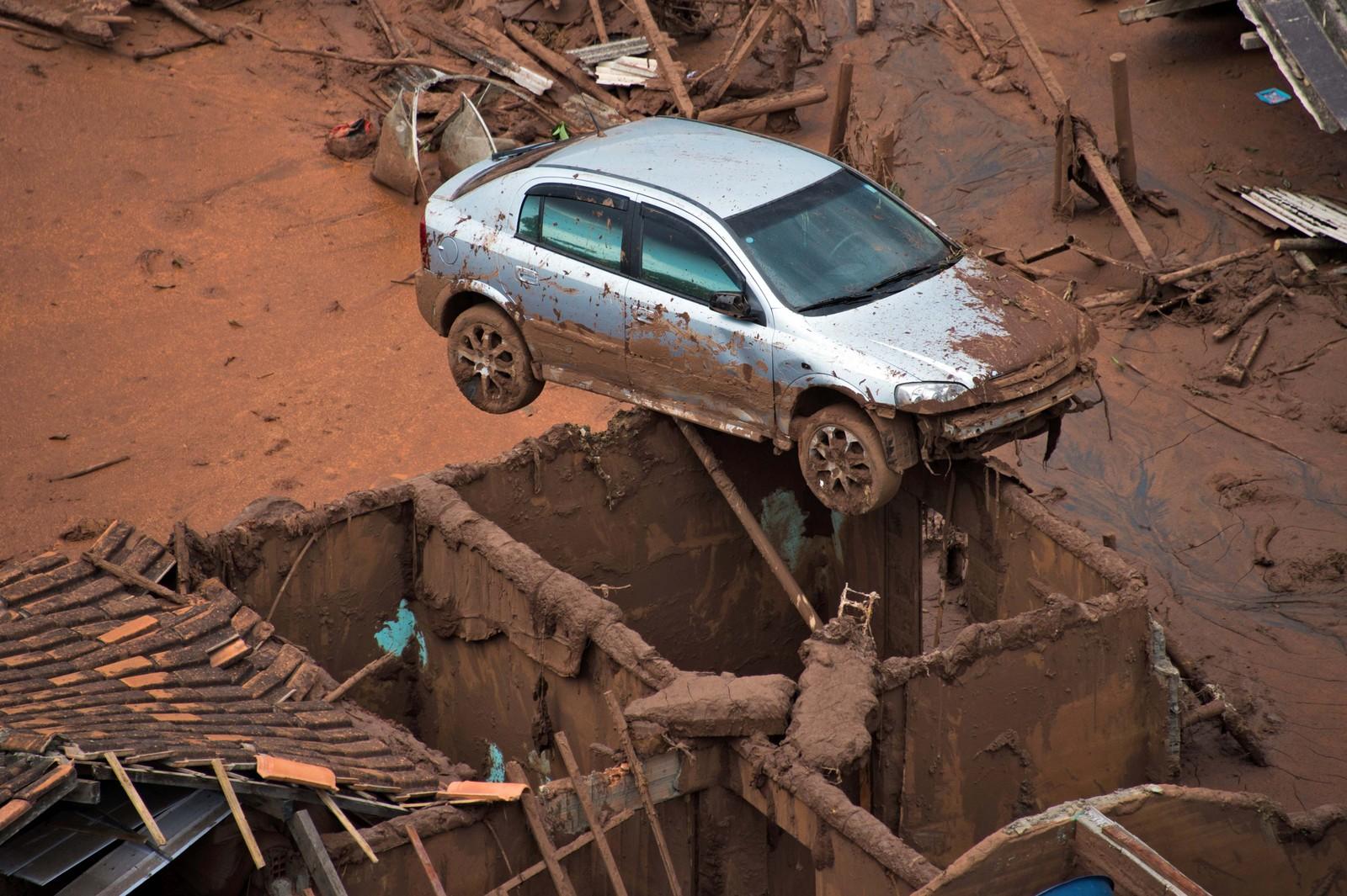 En bil henger nærmest i løse luften etter at en demning brast i landsbyen Bento Rodrigues i Brasil 6. november. Minst 17 personer mistet livet i ulykken og den giftige gjørmen som rant ut har skapt store miljøproblemer i området rundt.