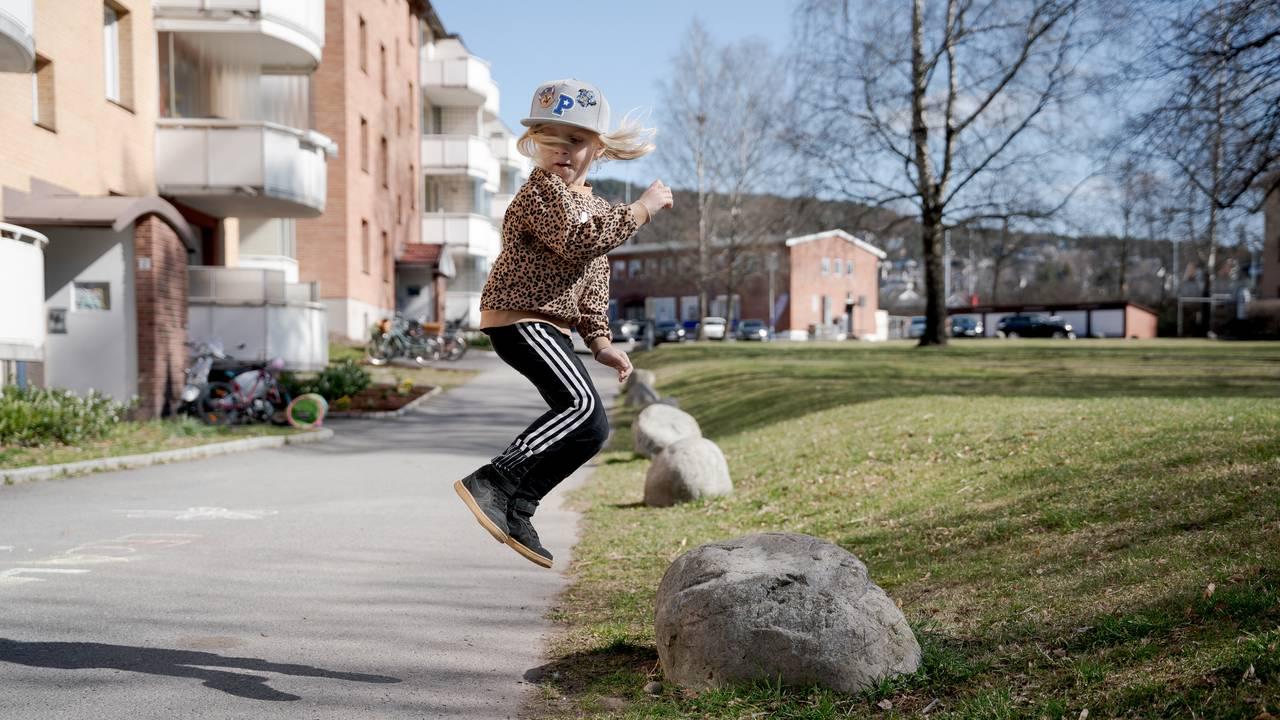 En lyshåret gutt hopper høyt opp foran boligblokker