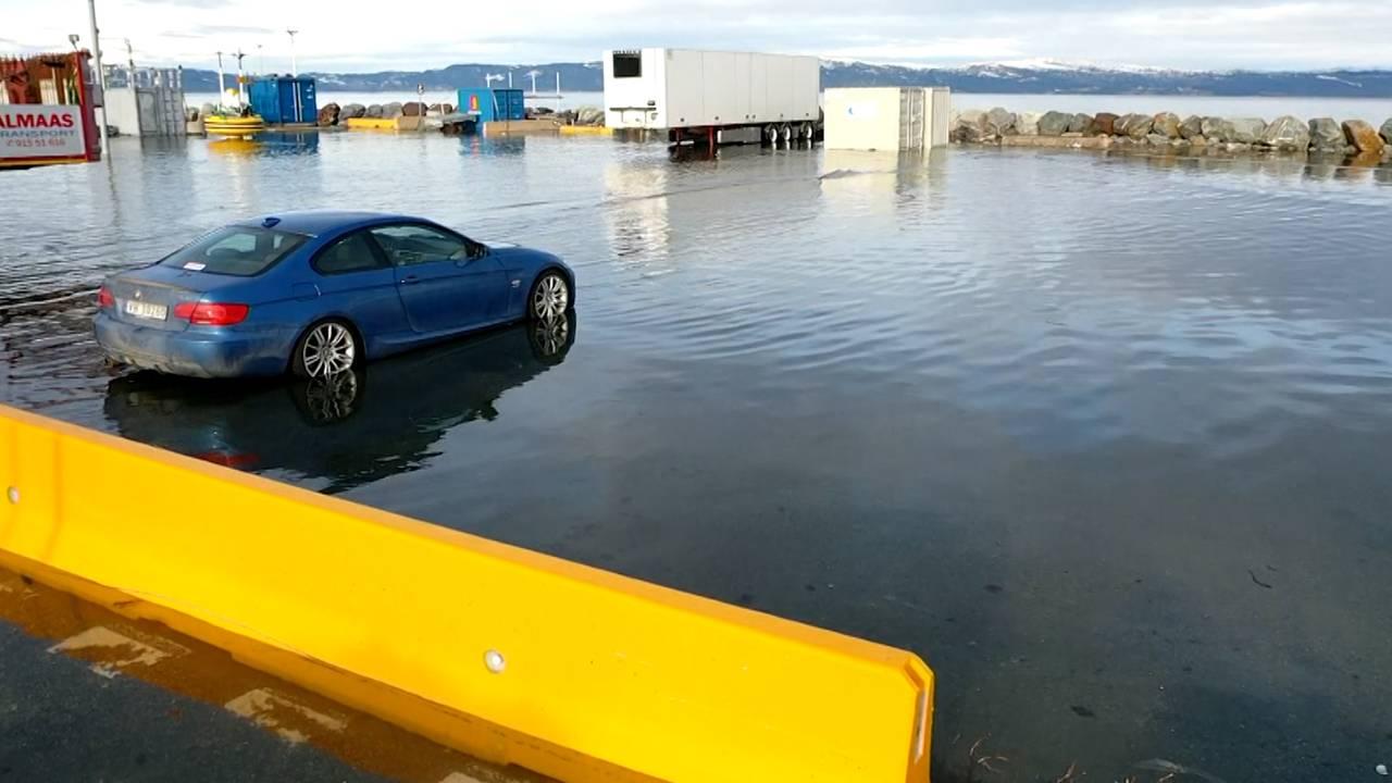 En bil står parkert på piren i Trondheim, med vann oppover dekkene.