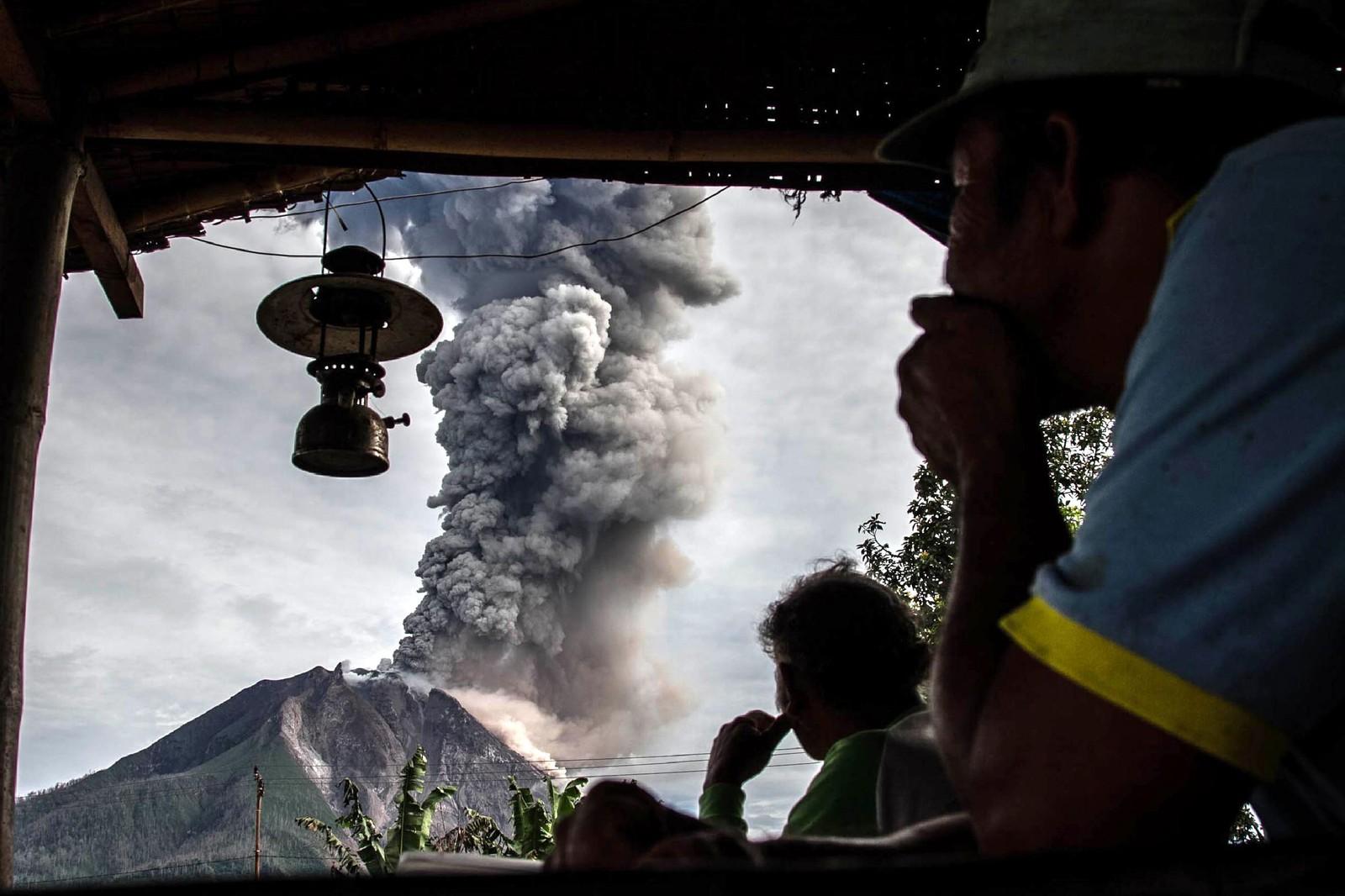 Landsbyboere fra Beganding på Nord-Sumatra i Indonesia ser på vulkanen Sinabung. Vulkanen våknet til liv igjen i 2010 etter å ha vært i dvale i rundt 400 år. Indonesia er det landet i verden med flest aktive vulkaner.