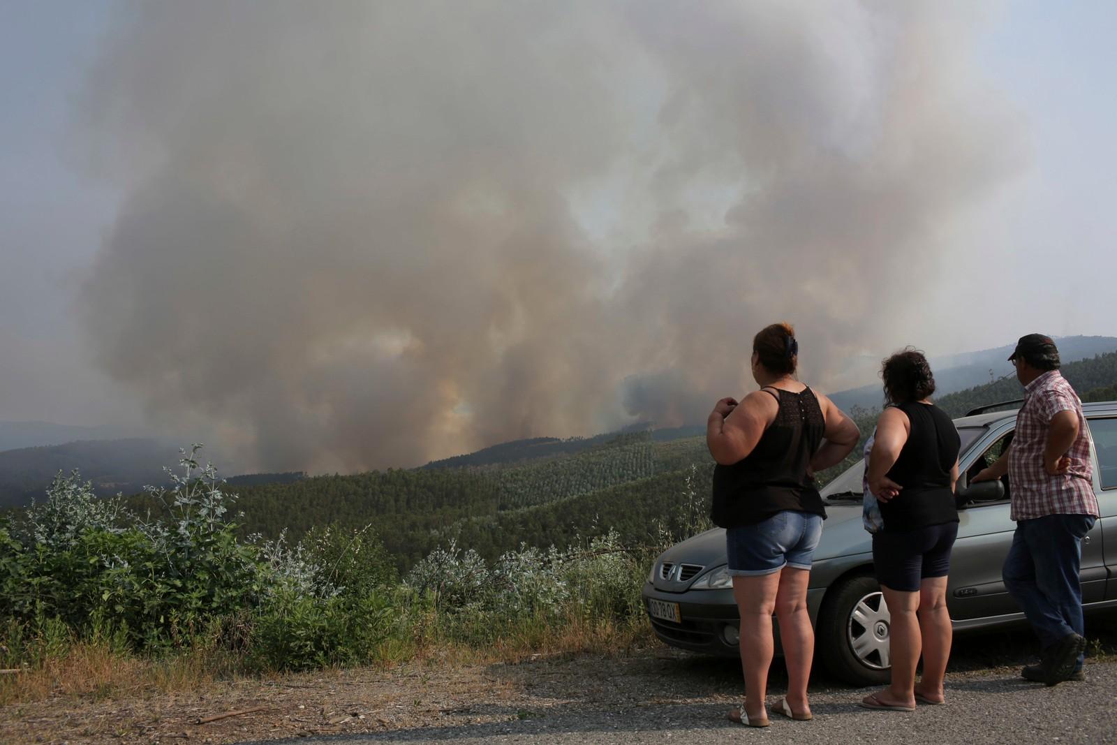Tilskuere ser brannen fra avstand 19. juni.
