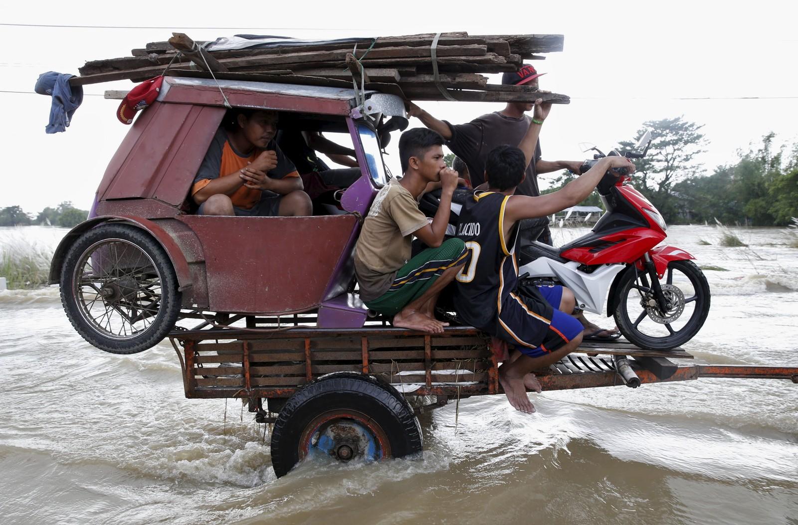 Unge fillippinere blir fraktet ut fra tyfon- og flomrammede Zaragoza på en henger bak en traktor.