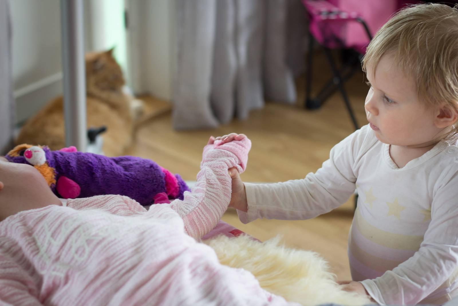 Amalie står på gulvet og tar tak i hånden til støresøster Frida Marie.
