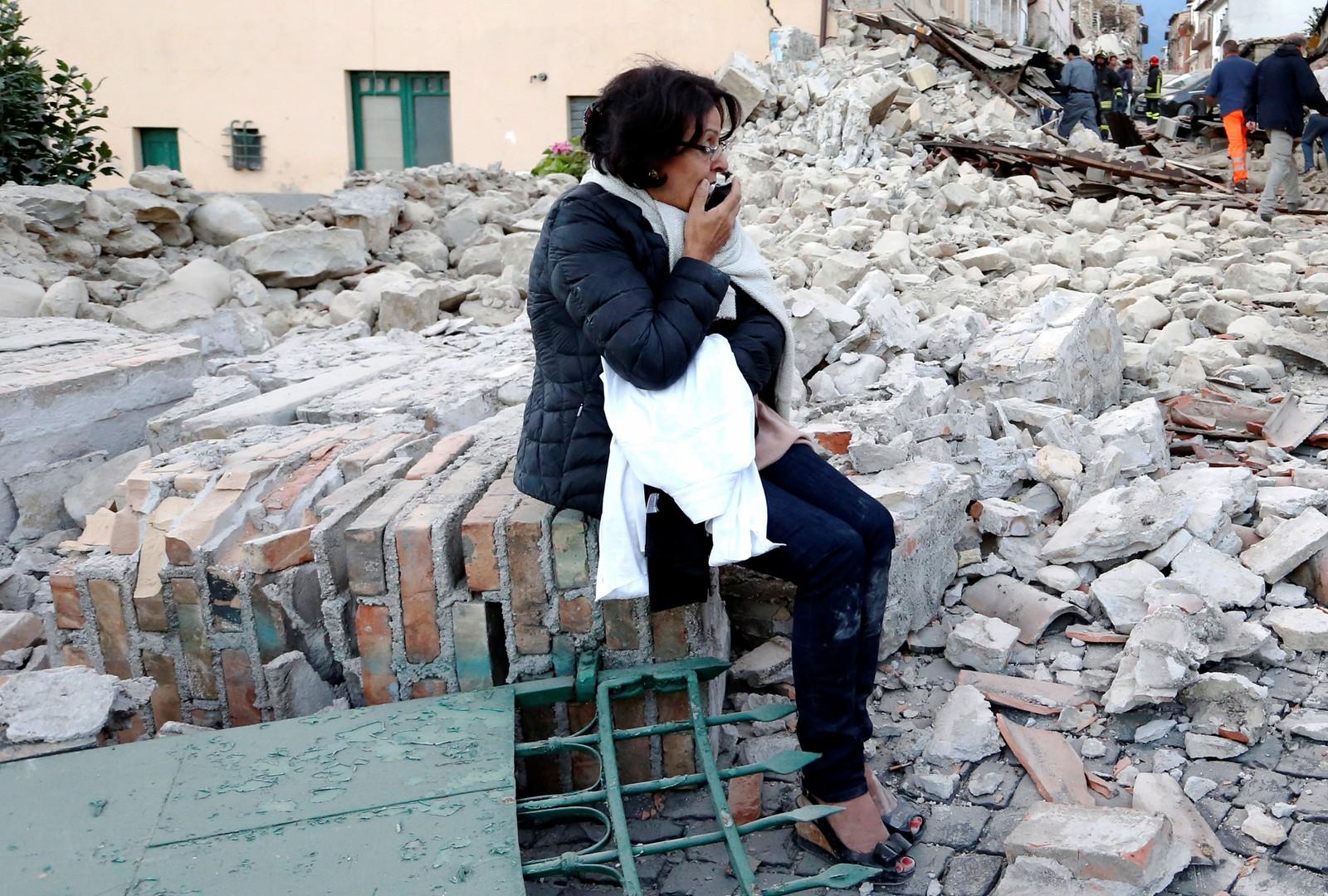 En kvinne skuer ut over ruinene i Amatrice.